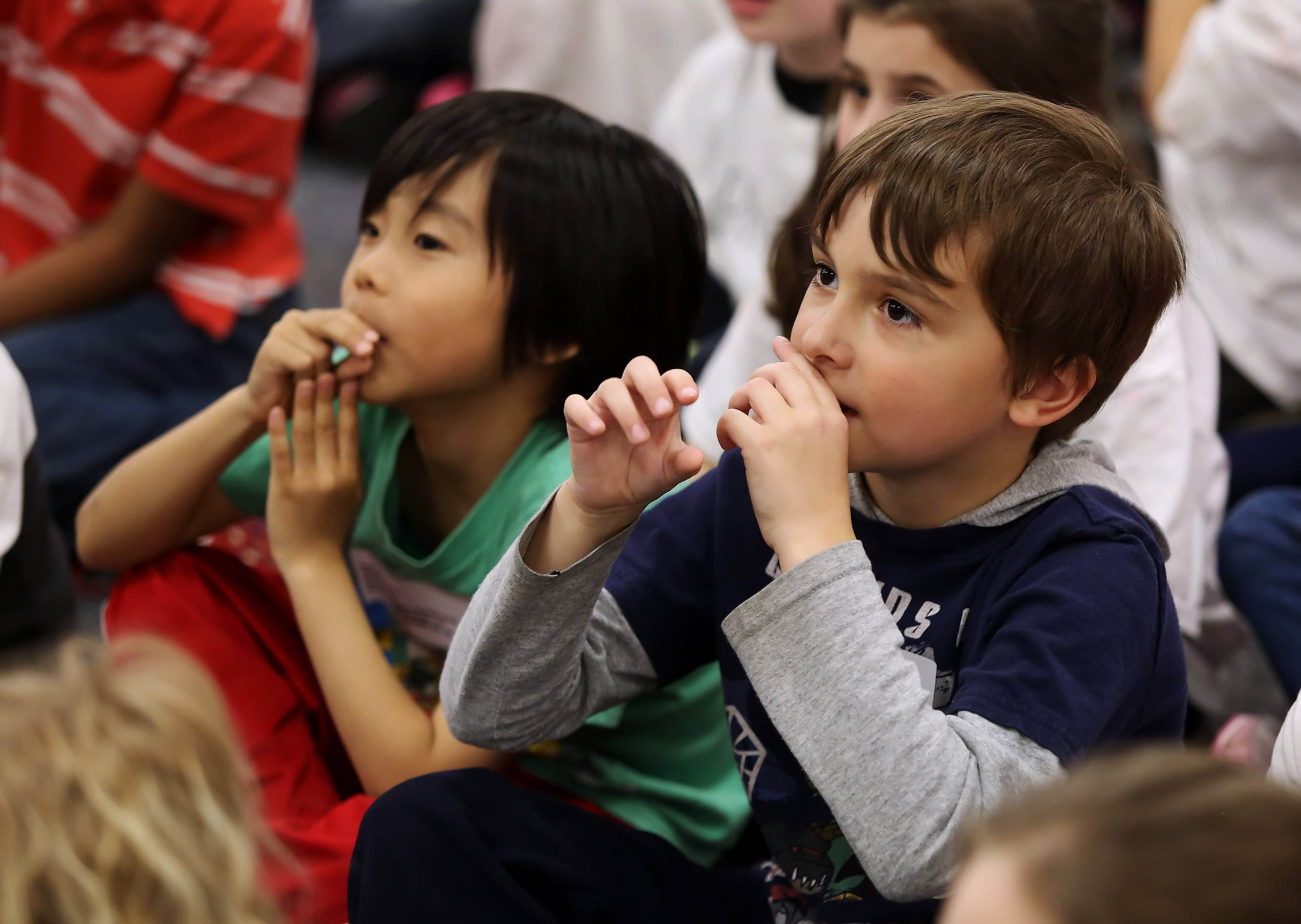 "Kindergartners Cuyler Hart, right, and Devin Lee pretend to play trumpets Thursday as they watch the Justin and Liam Show during ""Explore the Arts Day"" at Laura B. Sprague School in Lincolnshire. Students participated in workshops that included dance, art, music and theater."