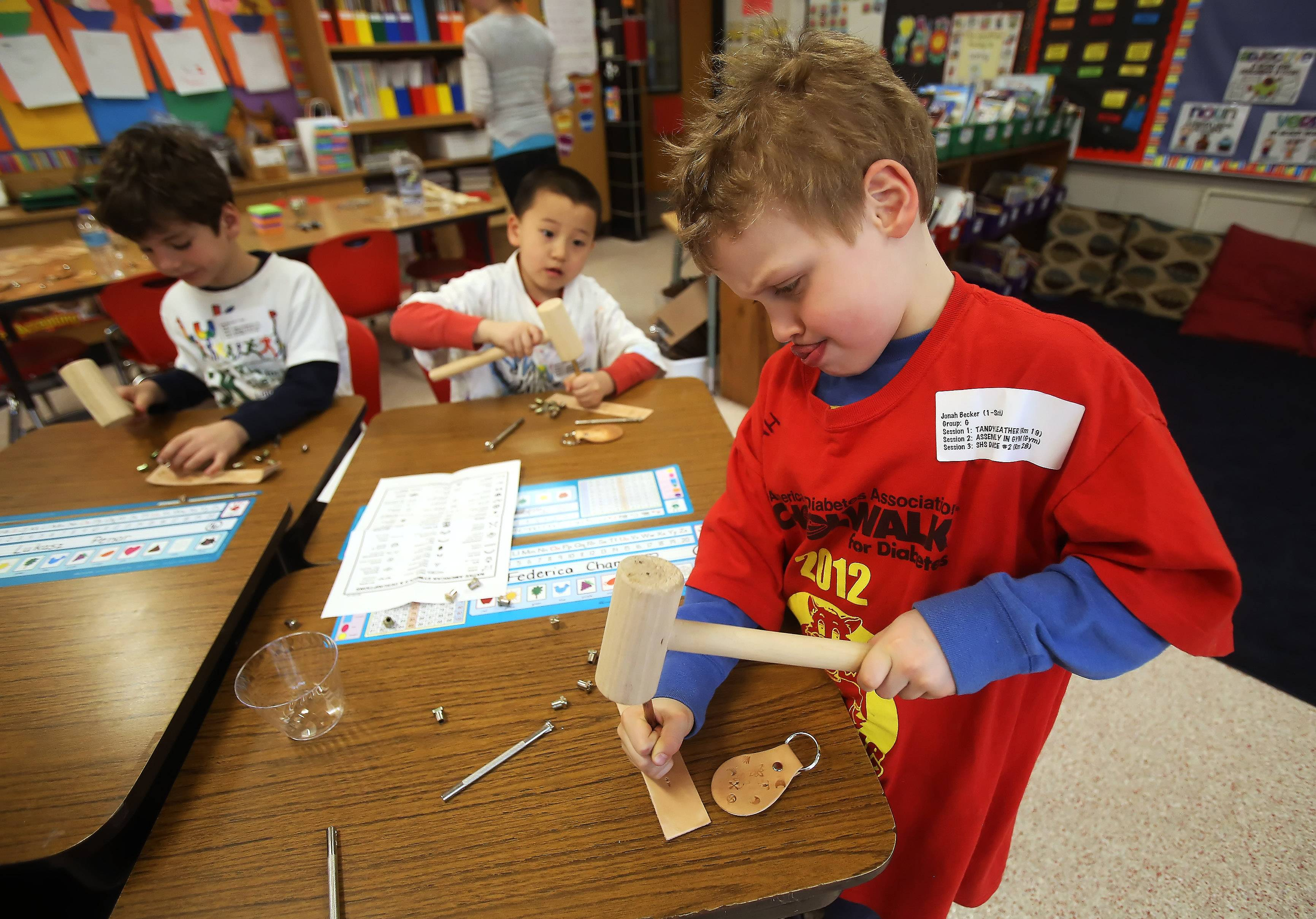 "First-grader Jonah Becker hammers with purpose in a leather stamping workshop Thursday during ""Explore the Arts Day"" at Laura B. Sprague School in Lincolnshire. Students participated in workshops that included dance, art, music and theater."