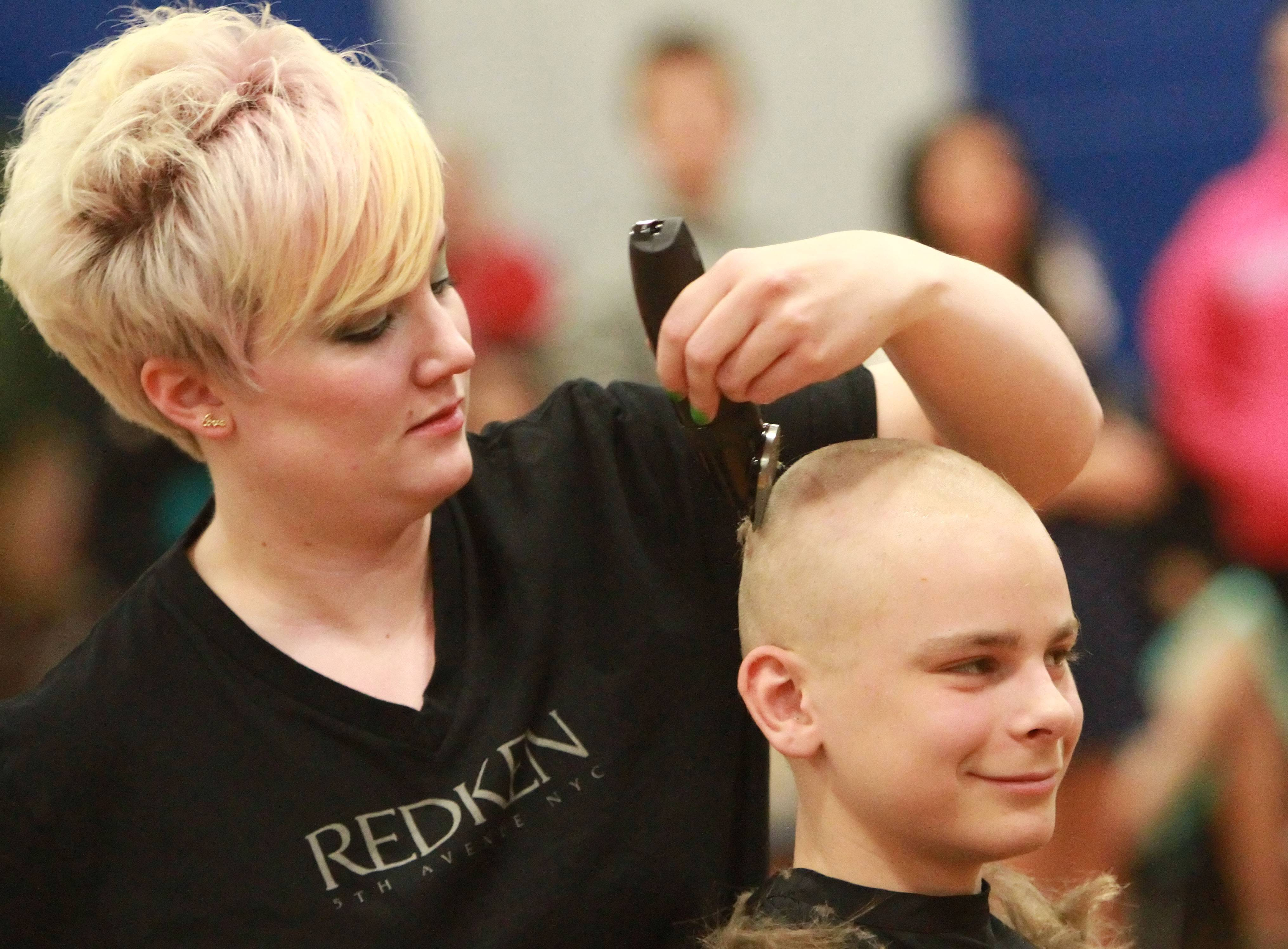 Mike Przybylski, 14, gets his head shaved Thursday by stylist Pam Meliksetyan of Legacy salon. spa during a St. Baldrick's assembly at Grayslake Middle School.