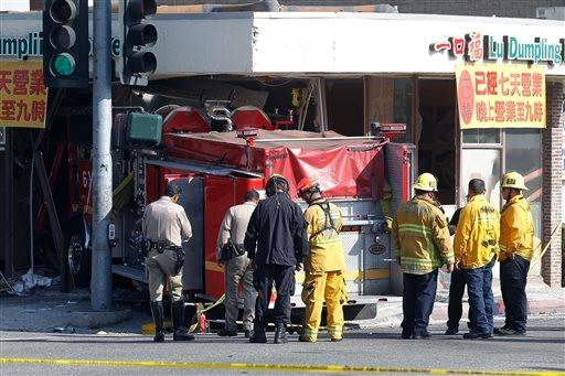 Firefighters and other officials work the scene of an accident where two firetrucks answering a call collided en route to a fire in Monterrey Park, Calif. The collision sent one firetruck careening into a restaurant, leaving 15 people injured, including several firefighters.