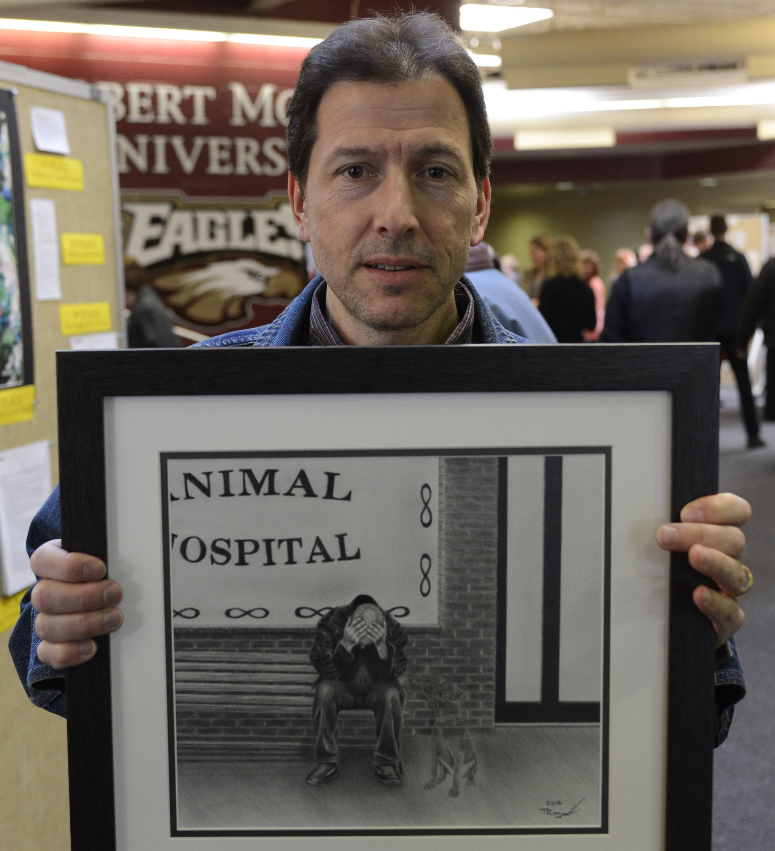 "Tim Trojan of Arlington Heights shows the original print of his work ""Goodbye Old Friend"" during the annual Arts Unlimited reception and program Wednesday at Forest View Education Center in Arlington Heights."