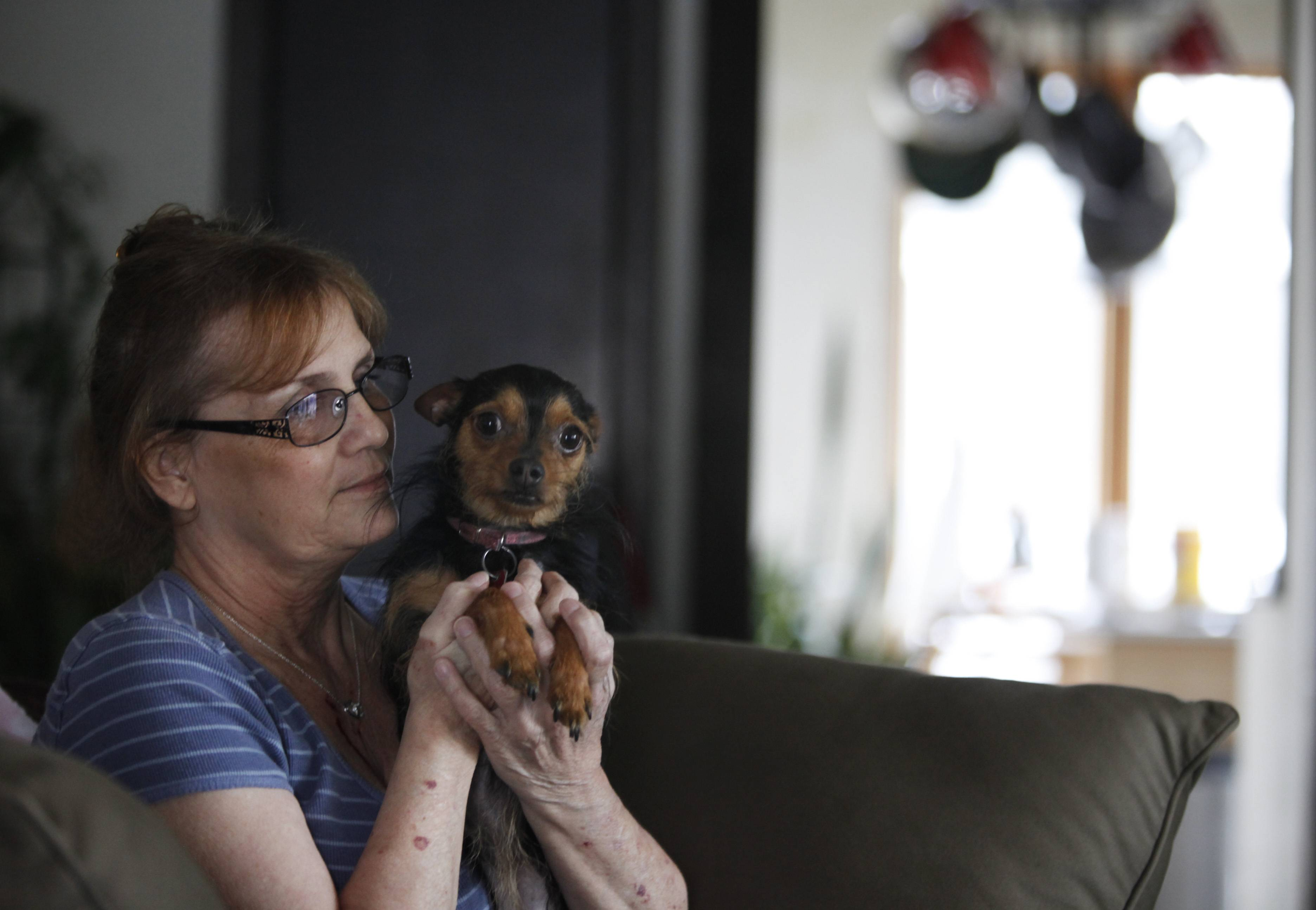 Barrie Komorski of unincorporated Kane County near East Dundee, and her dog, Roxi, were rescued from flooding outside her home along Fox River Drive last spring. Despite a crawl space beneath her home that was flooded and potentially damaged, and losing her unemployment benefits from a job she lost in 2012, Komorski has no plans to leave the flood-prone area.