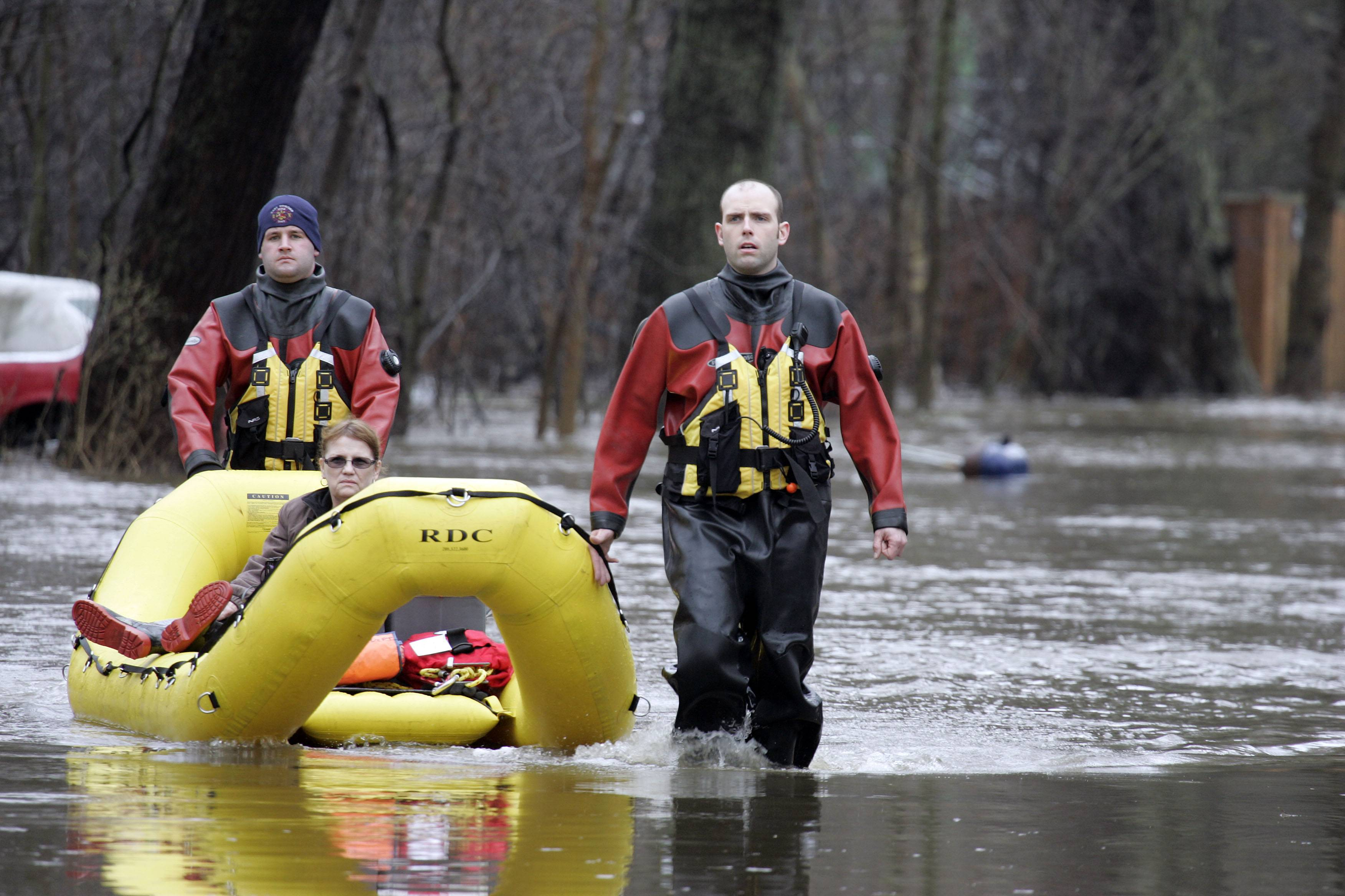 "Firefighters Nick Beauchaine, left, and Lt. Jason Parthun, of the East Dundee Fire Protection District, escort Barrie Komorski and her dog, Roxi, from her home in a boat after flooding on the Fox River last April caused voluntary evacuation from the Richardson subdivision. ""I normally would have stayed but they shut off the gas so I had to leave because of my dog,"" Komorski said."