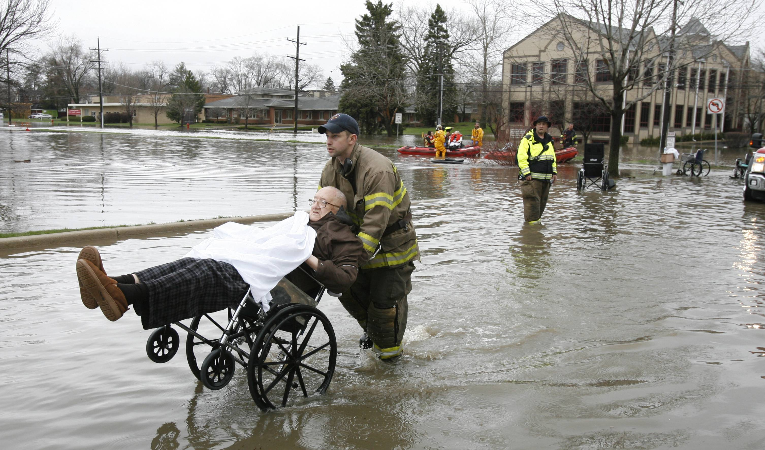 Firefighters help evacuate residents of Snow Valley Nursing and Rehabilitation Center in Lisle last April 18 after the building on Route 53 flooded.