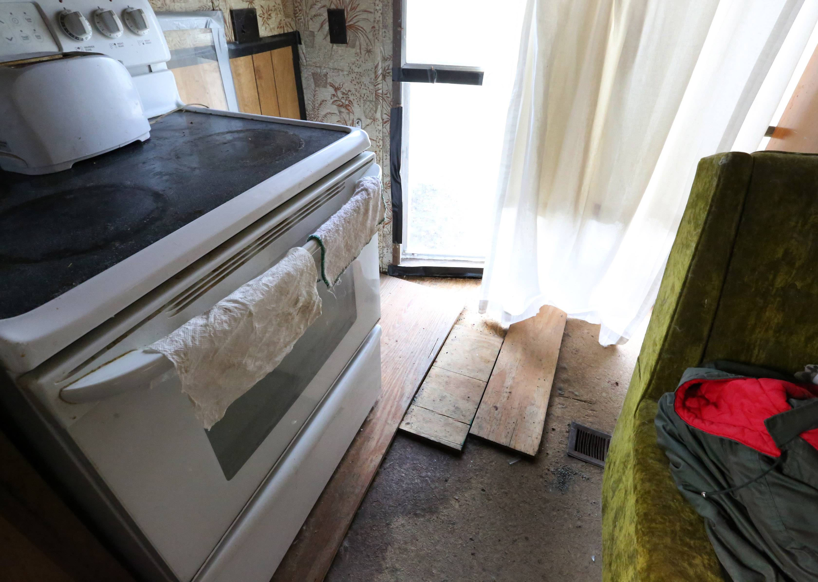 After floodwaters gushed through windows in the kitchen of this mobile home, owner Michael Masalski put boards on the floor to cover the rotted areas.