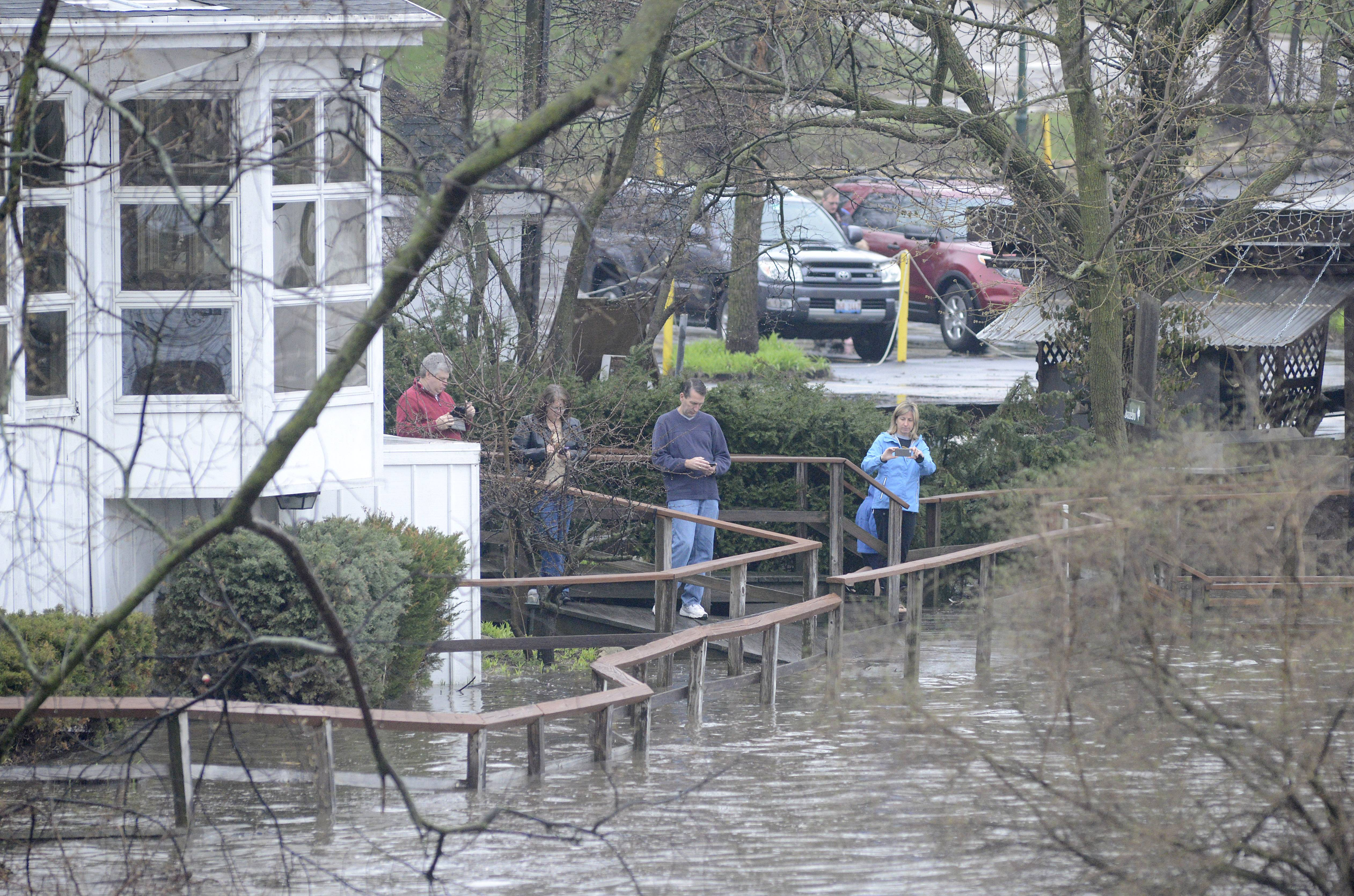People gather on the boardwalk outside the shuttered Mill Race Inn next to Island Park in Geneva to photograph the floodwaters on Thursday, April 18. A constant flow of cars came into and out of the parking lot to get a glimpse of the racing waters.