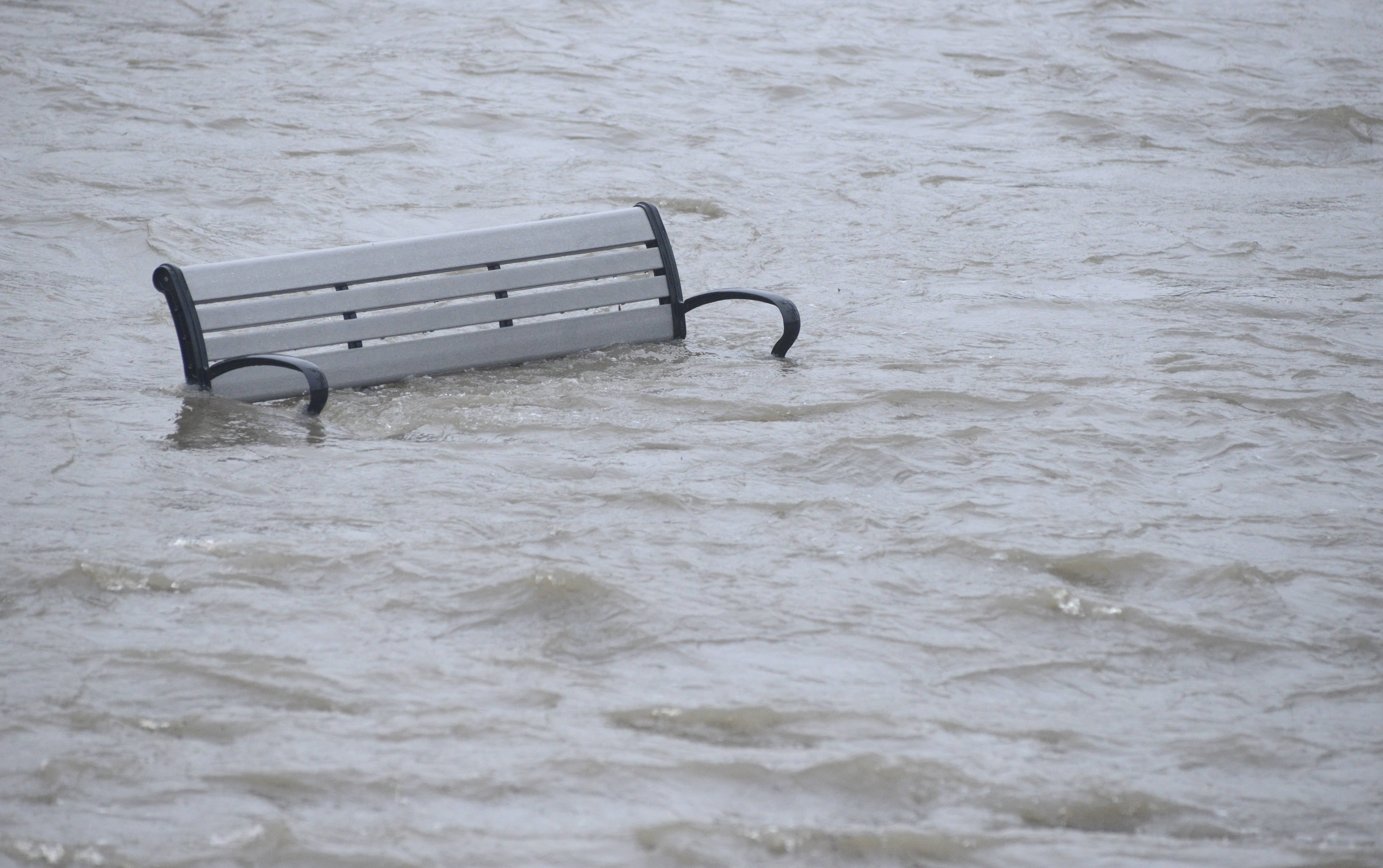One of several benches in Island Park submerged by the racing floodwaters of the Fox River in Geneva on Thursday, April 18.