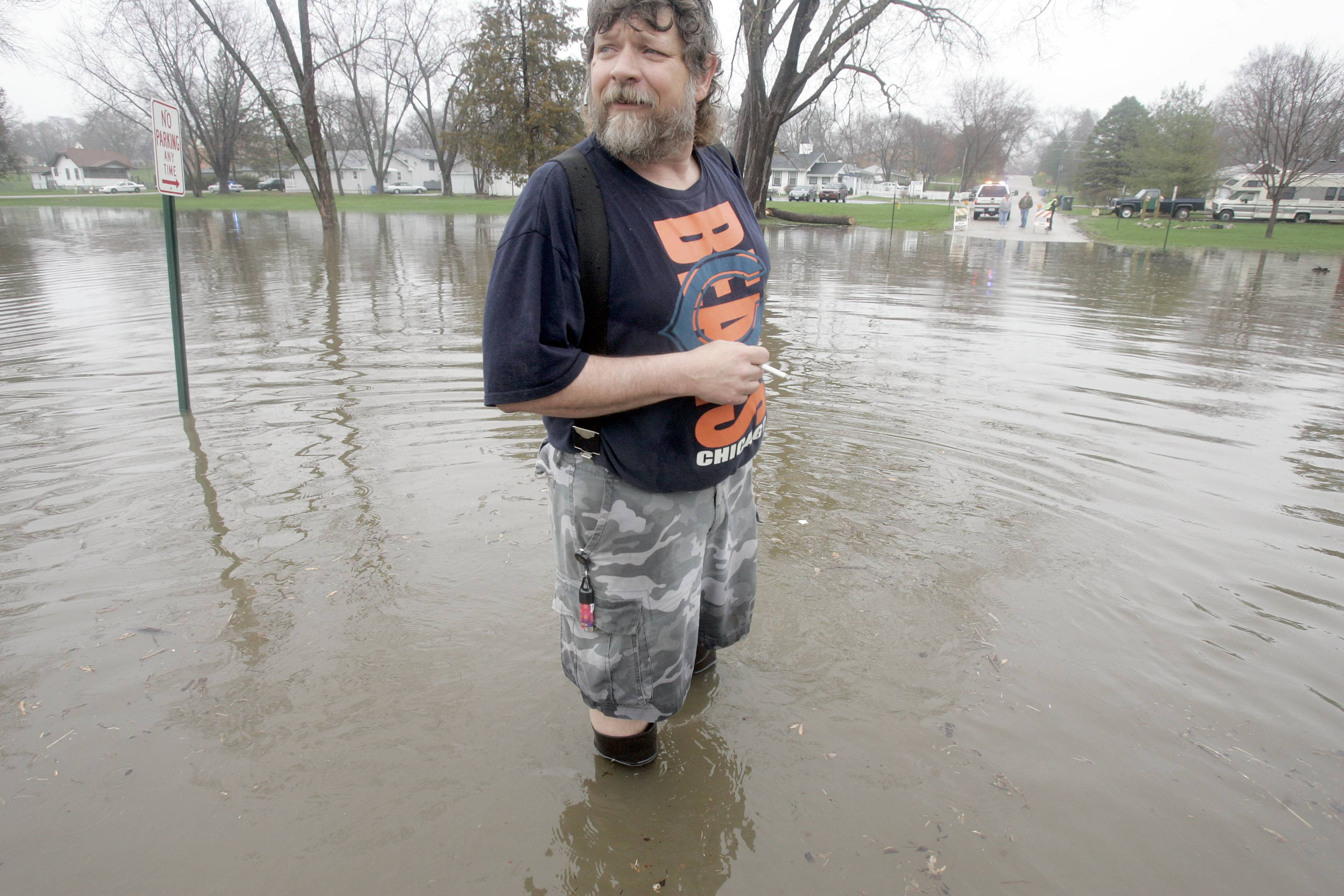 Mike Brancecum of South Elgin stands knee deep in flood water just East of his home on East Spring Ave in South Elgin after flooding on the Fox River Thursday in South Elgin.