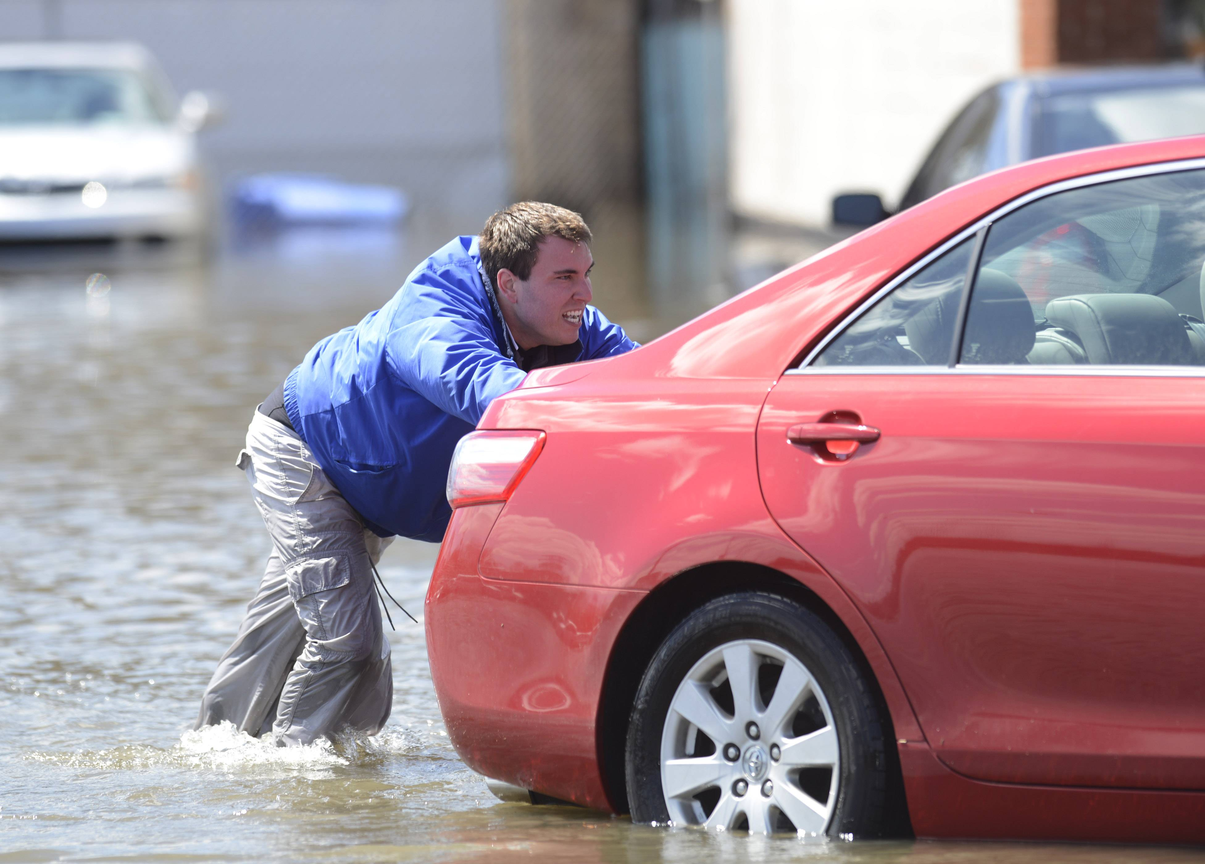 Rob Burns helps push an auto from a flooded used car lot toward higher ground in Des Plaines Saturday. Burns and his partner avoided running the operable cars in the higher water, then started them once they were safely on higher ground.