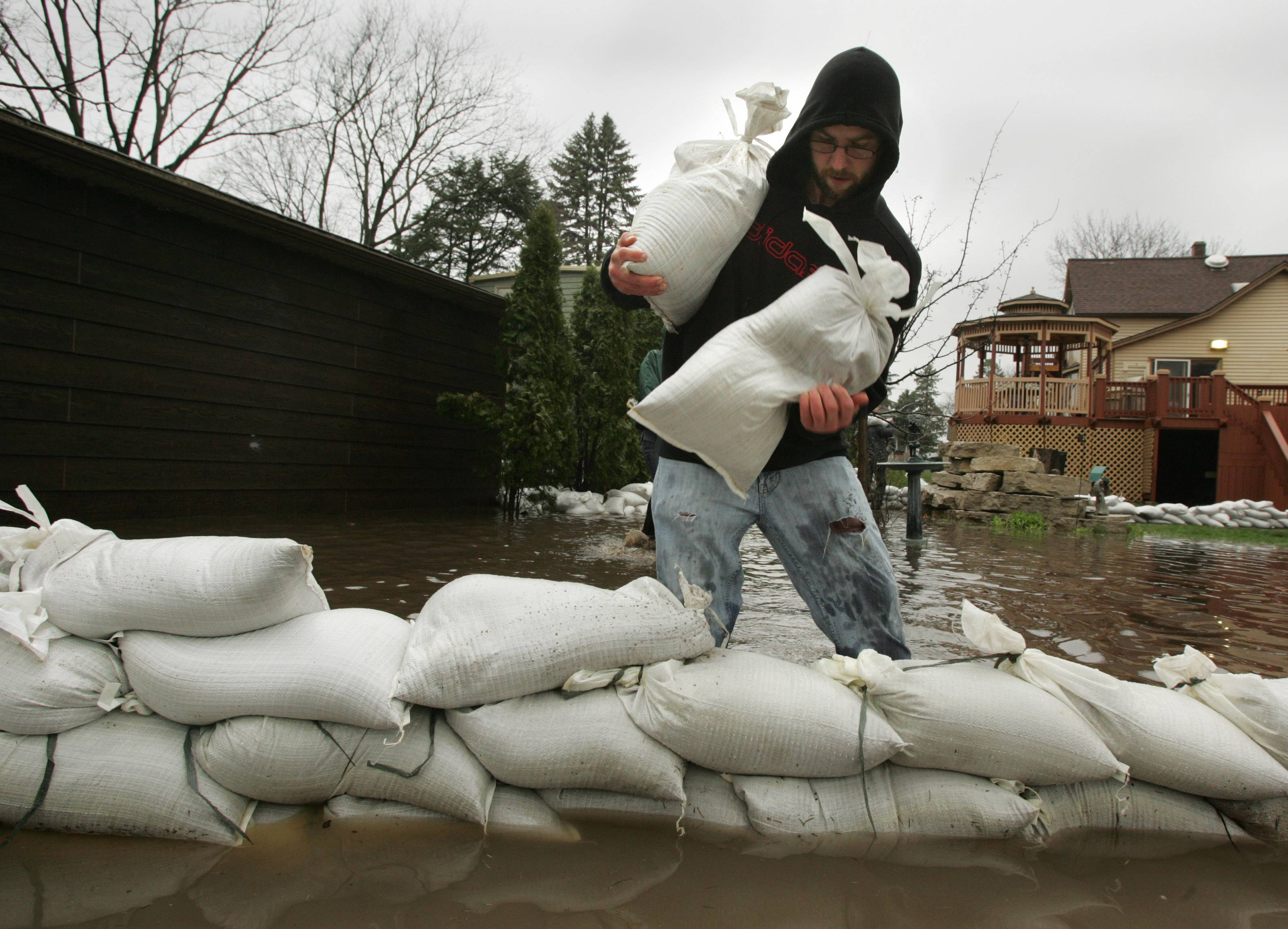 Eric Johnson of Lake in the Hills helps add more sandbags behind a home on in Algonquin along the west side of the Fox River Thursday morning.