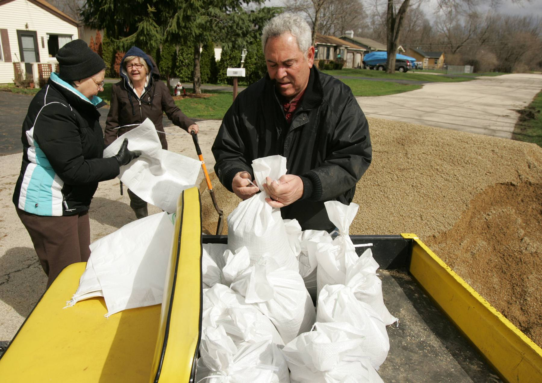 Nick Gagliano ties sand bags as his wife Nan, center, and neighbor Yvonne Dragon, left, load more so he can place them along his home where the current from the Fox River is rushing up against the foundation.