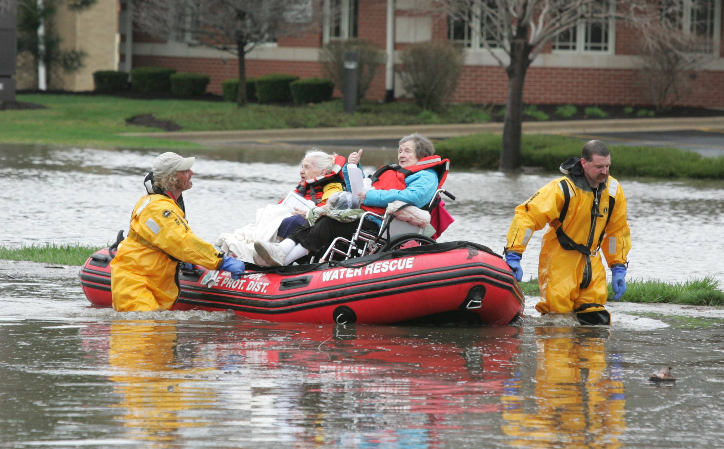 Flooding along Rt. 53 forces the evacuation of residents of the Snow Valley Nursing and Rehabilitation Center in Lisle. Above, Big Rock Fire Protection District Firefighters Steve Weissinger, left, and Jason Halstead, right, evacuated numerous patients.