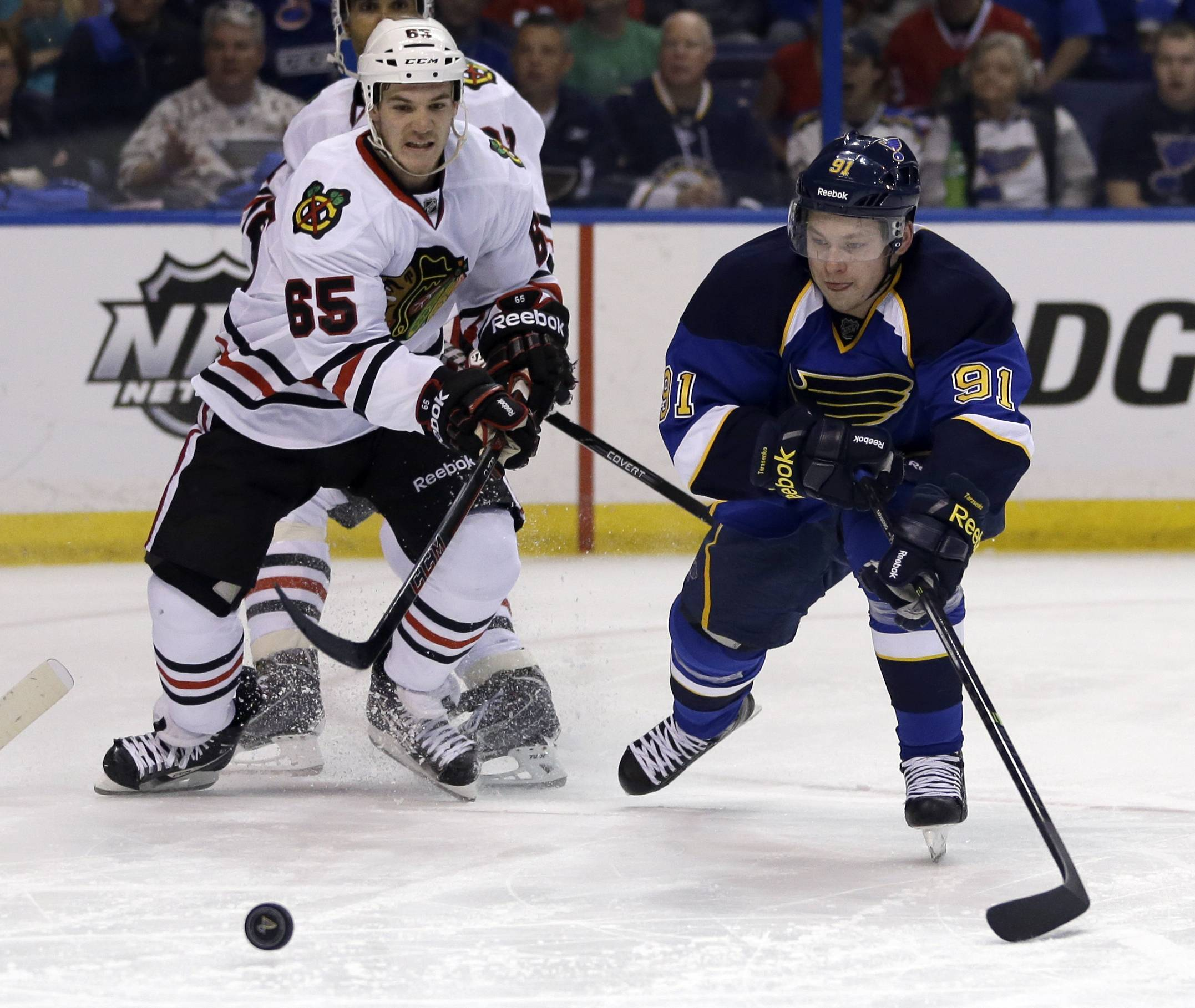Chicago Blackhawks' Andrew Shaw, left, and St. Louis Blues' Vladimir Tarasenko chase a loose puck during the second period.
