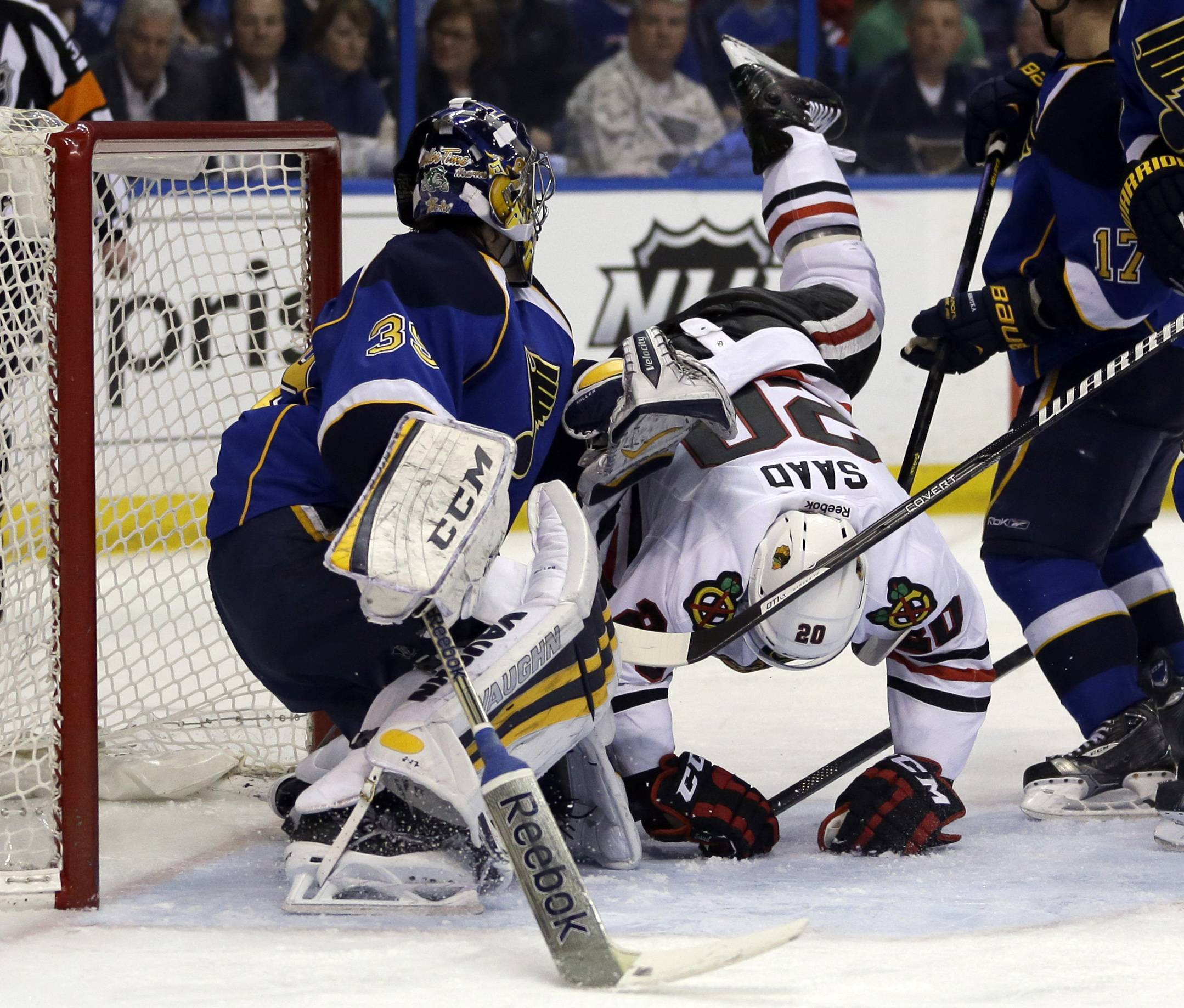 Chicago Blackhawks' Brandon Saad (20) loses his footing as St. Louis Blues goalie Ryan Miller watches during the third period.
