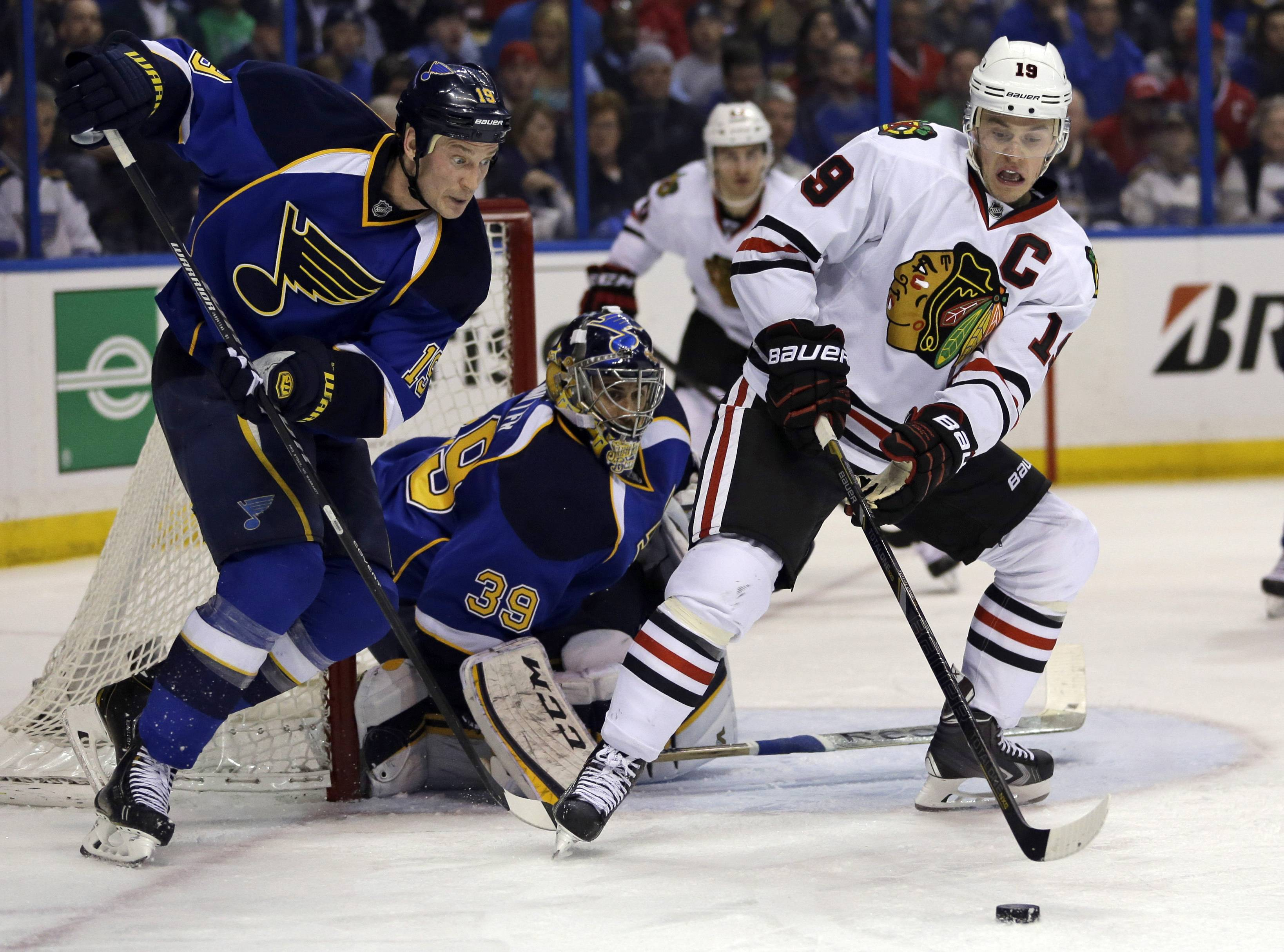 Chicago Blackhawks' Jonathan Toews, right, controls the puck as St. Louis Blues goalie Ryan Miller and Jay Bouwmeester, left, defend during the third period.