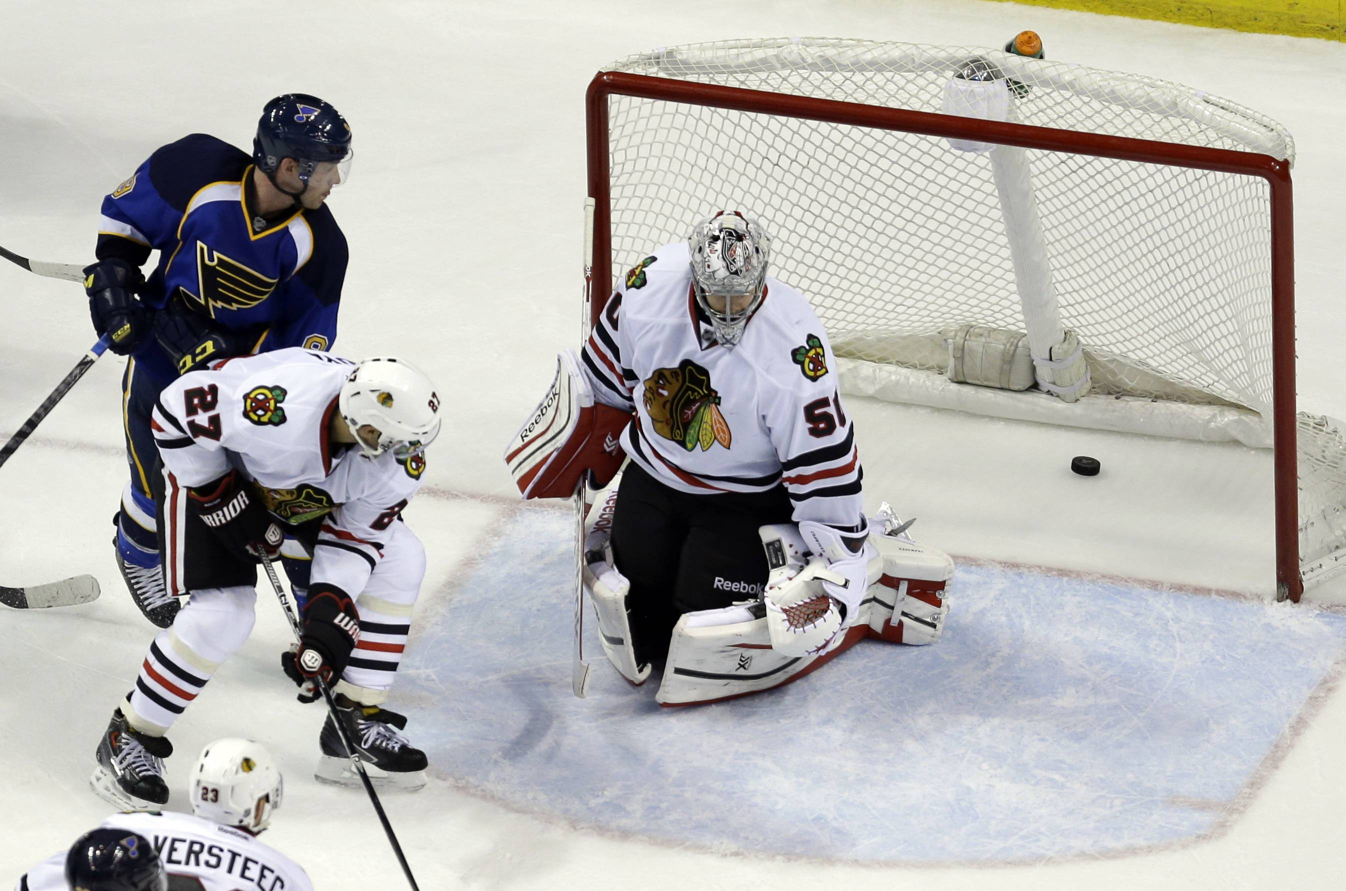 St. Louis Blues' Jaden Schwartz, top left, watches as his shot slips past Chicago Blackhawks goalie Corey Crawford and Johnny Oduya (27) for a goal during the third period.