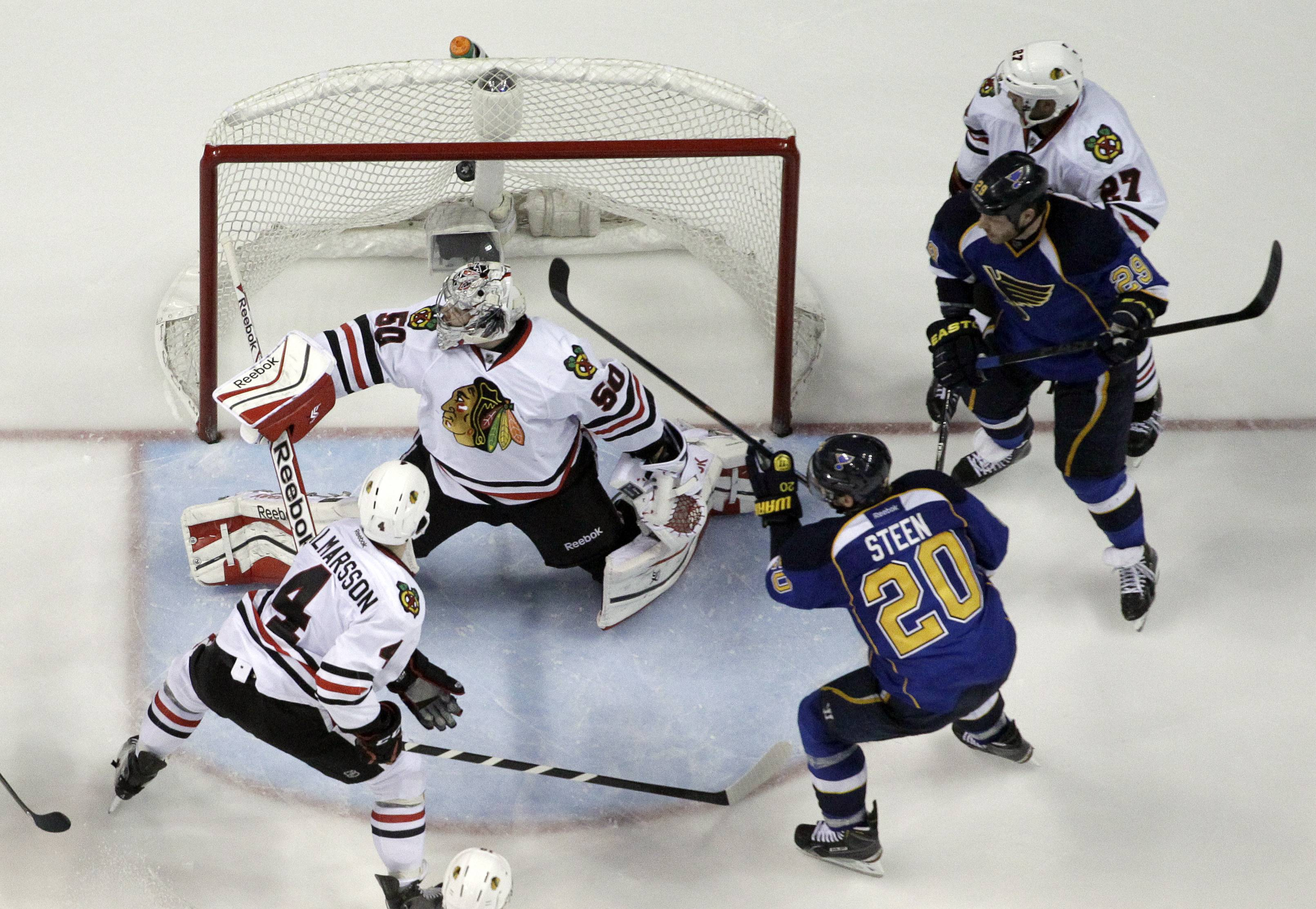 St. Louis Blues' Alexander Steen (20) scores the game-winning goal past Chicago Blackhawks goalie Corey Crawford and Niklas Hjalmarsson .The Blues won 4-3 in triple overtime.
