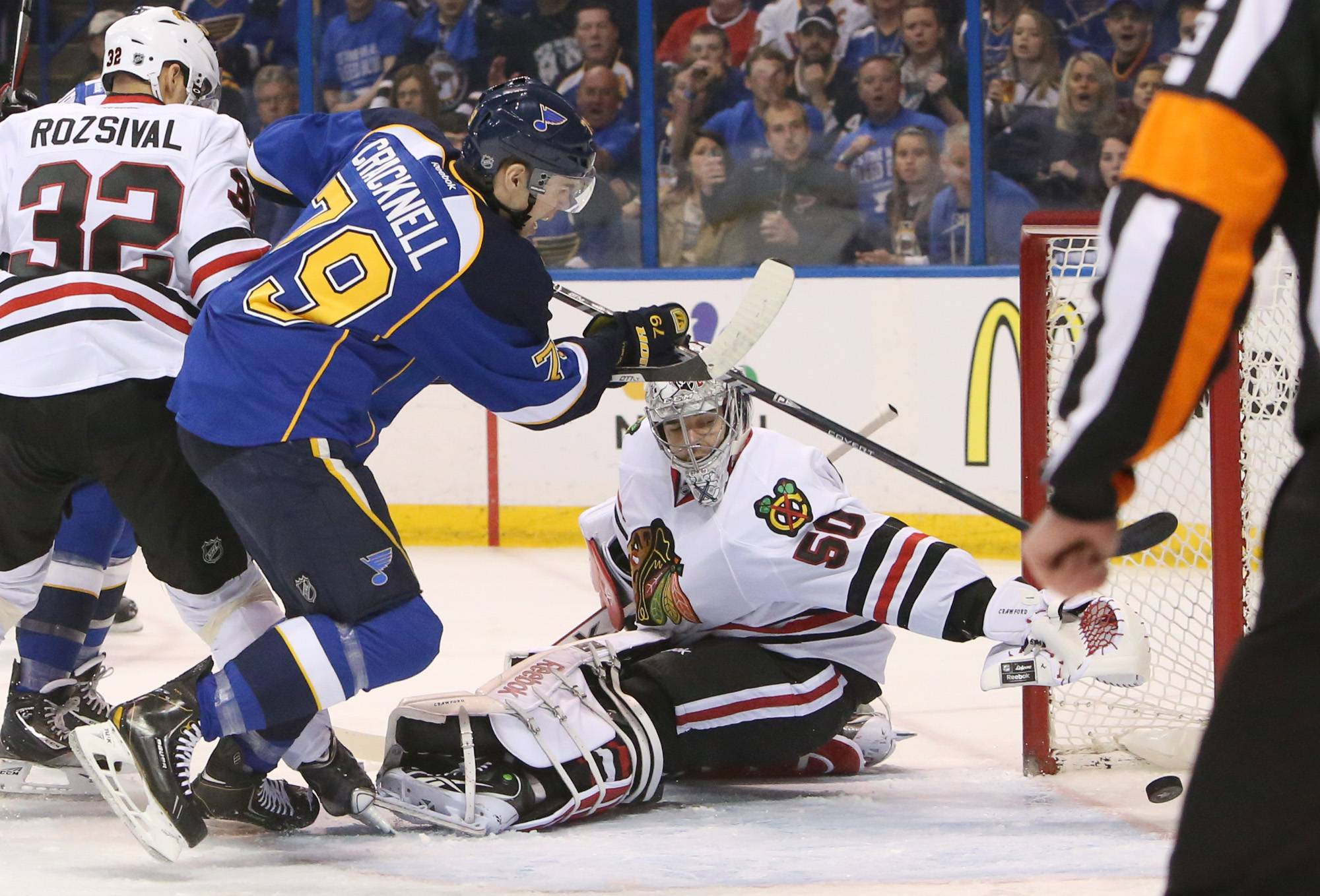 St. Louis Blues right wing Adam Cracknell, left, scores past Chicago Blackhawks goaltender Corey Crawford during the first period.