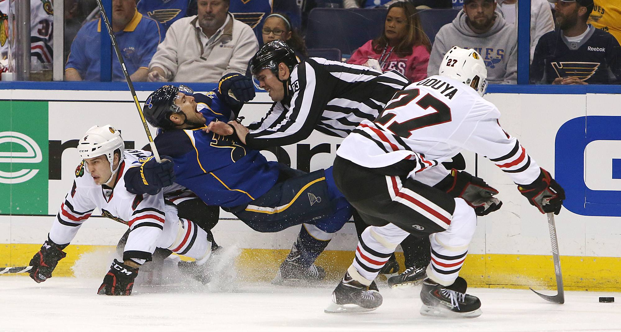 St. Louis Blues left wing Chris Porter loses possession of the puck as he is sandwiched between Chicago Blackhawks defenseman Niklas Hjalmarsson, left, and linesman Matt MacPherson during the first period .At right is Blackhawks' Johnny Oduya.