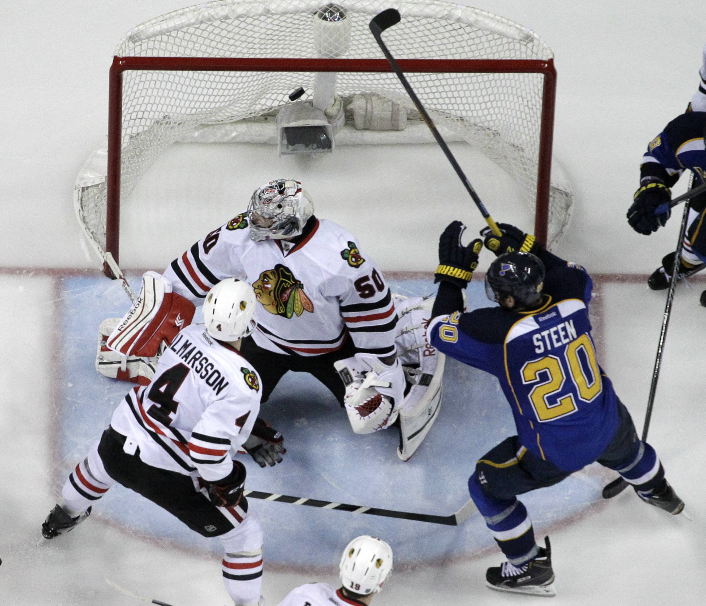 St. Louis Blues' Alexander Steen (20) scores the game-winning goal past Chicago Blackhawks goalie Corey Crawford and Niklas Hjalmarsson (4) during the third overtime in Game 1 of a first-round NHL hockey Stanley Cup playoff series Thursday, April 17, 2014, in St. Louis. The Blues won 4-3 in triple overtime.