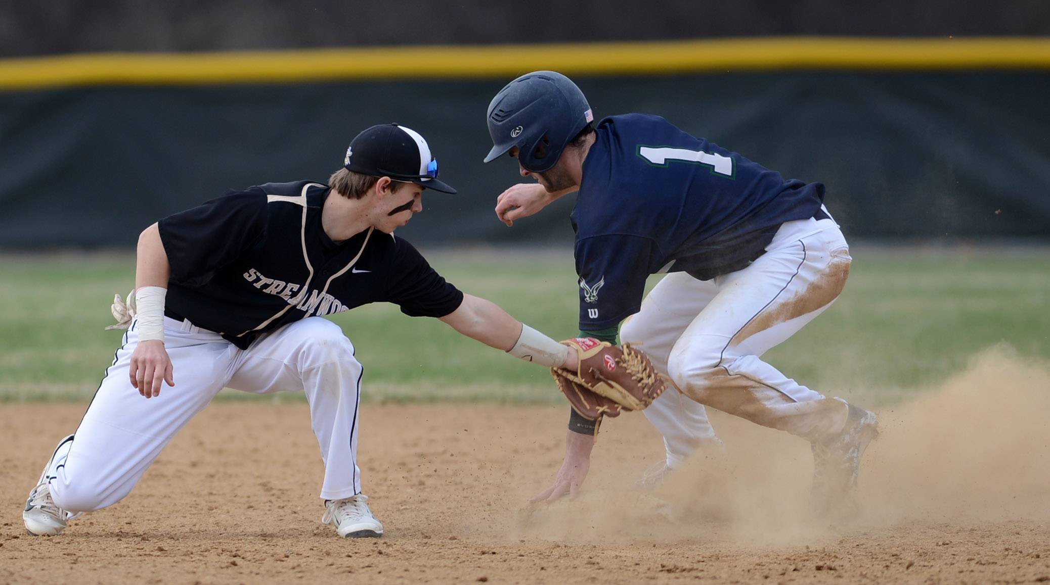 Streamwood's Chad Caminitti turns and swipes a tag but Bartlett's Mike Wick (1) is already safe at second with a steal during Thursday's game in Bartlett.