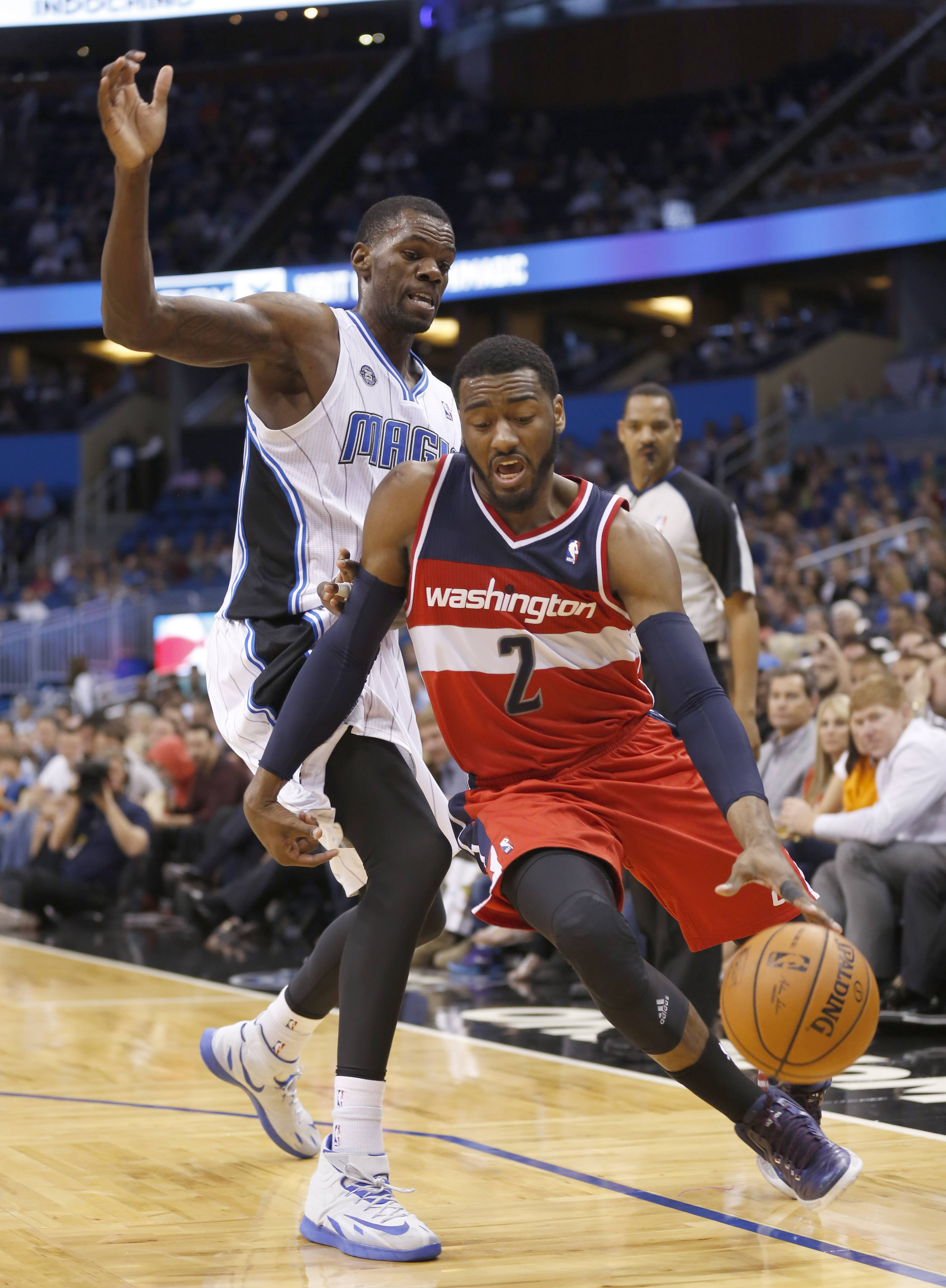 Wizards guard John Wall drives past Orlando Magic center Dewayne Dedmon during the first half of an NBA basketball game in Orlando, Fla., Friday, Apr. 11, 2014.