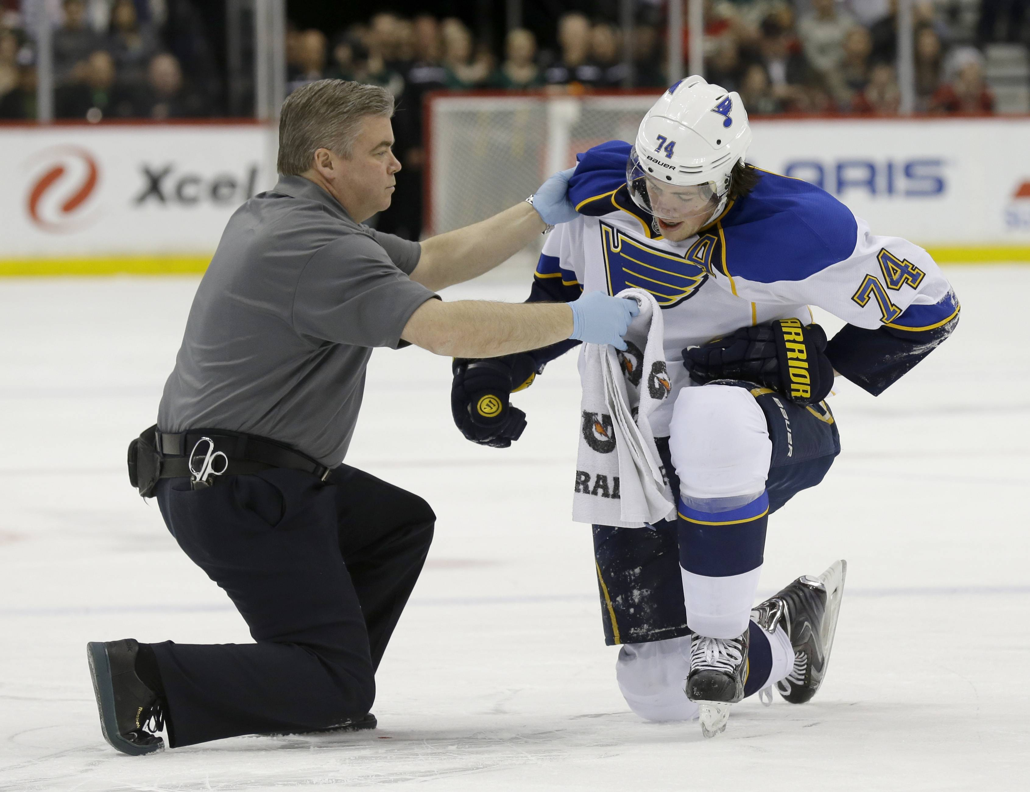 St. Louis Blues right wing T.J. Oshie (74) tries to get up with help from a trainer but can't after being injured during the second period of an NHL hockey game against the Minnesota Wild in St. Paul, Minn., Thursday, April 10, 2014.
