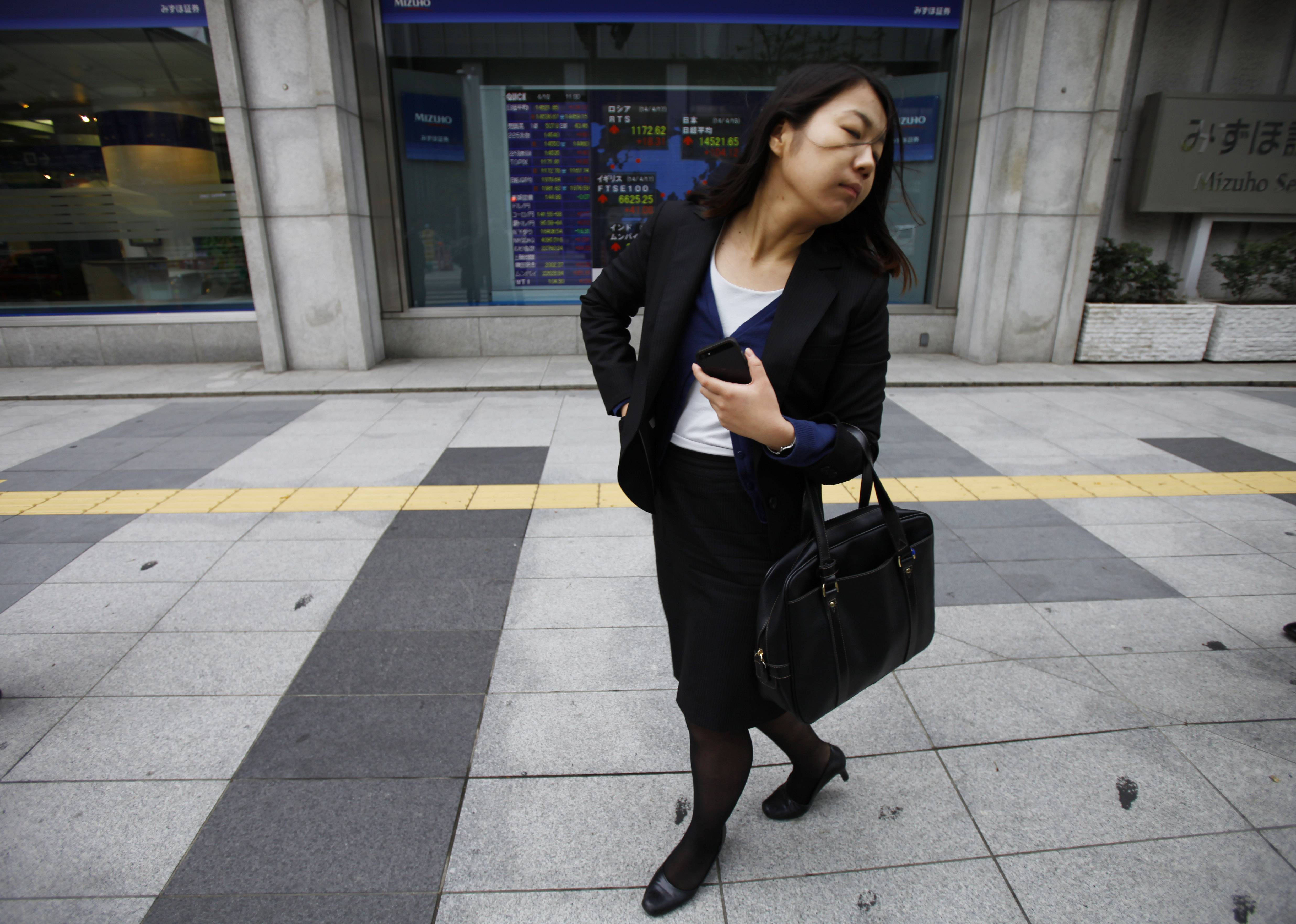A woman walks Friday by an electric stock board outside a securities firm in Tokyo. Asian stocks were mostly higher Friday after mixed U.S. earnings reports with most of the region's exchanges closed for Good Friday. Tokyo's Nikkei 225 gained 0.6 percent to 14,504.47.