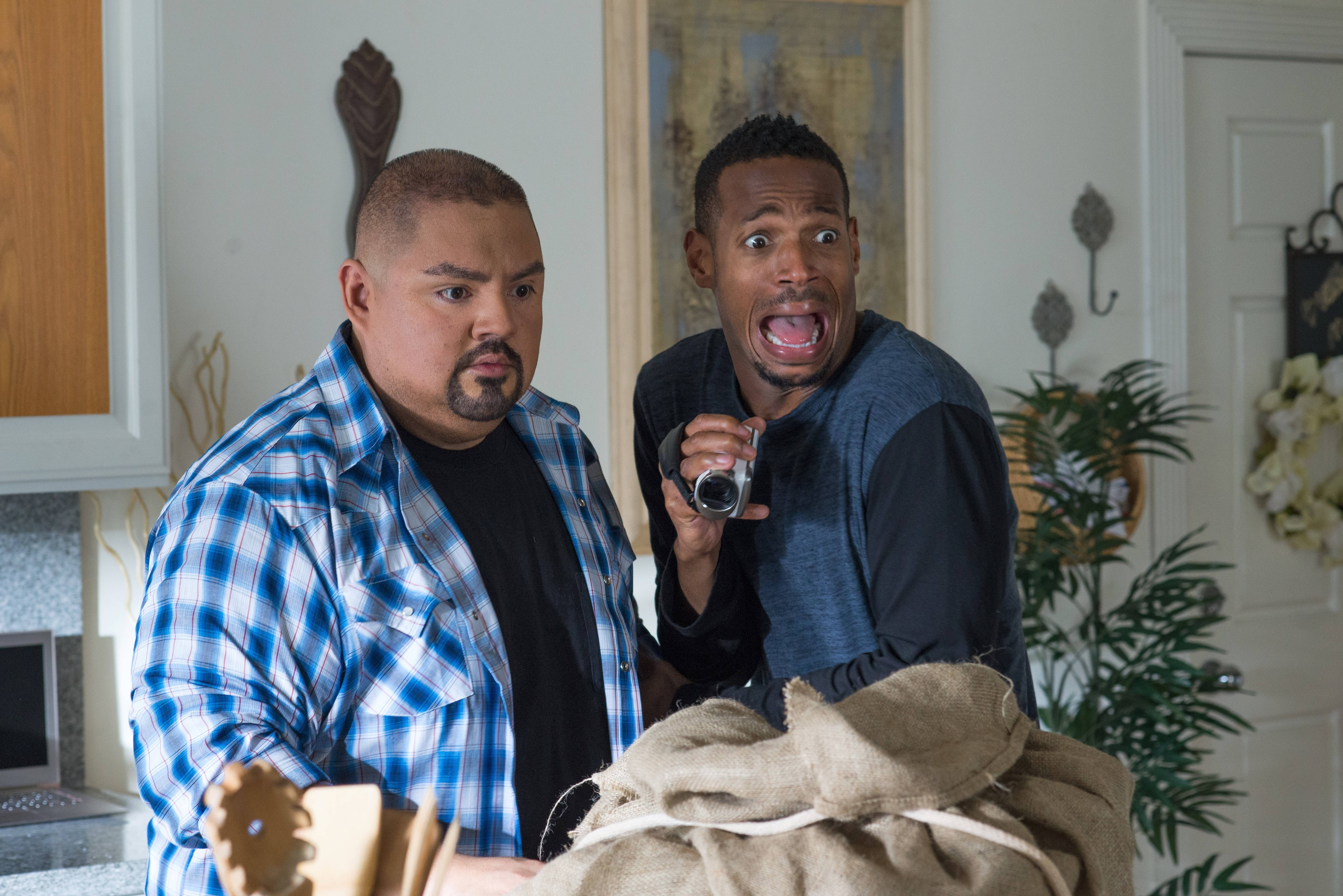 "Malcolm (Marlon Wayans, right) involves his neighbor (Gabriel Iglesias) when weird things start happening in ""A Haunted House 2."""