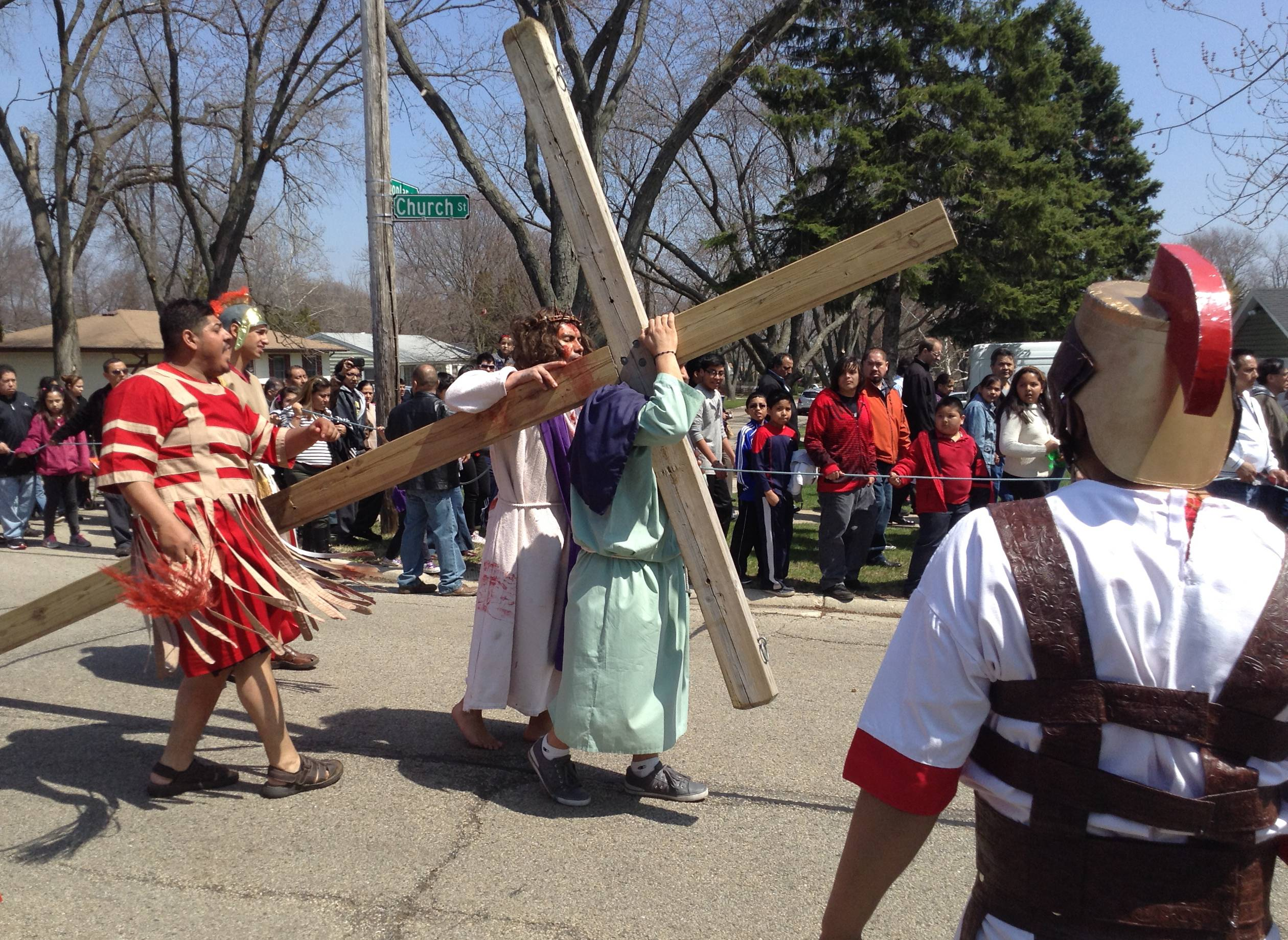 A barefoot Isidro Zuniga carried a wooden cross for more than mile through a Hanover Park neighborhood Friday.