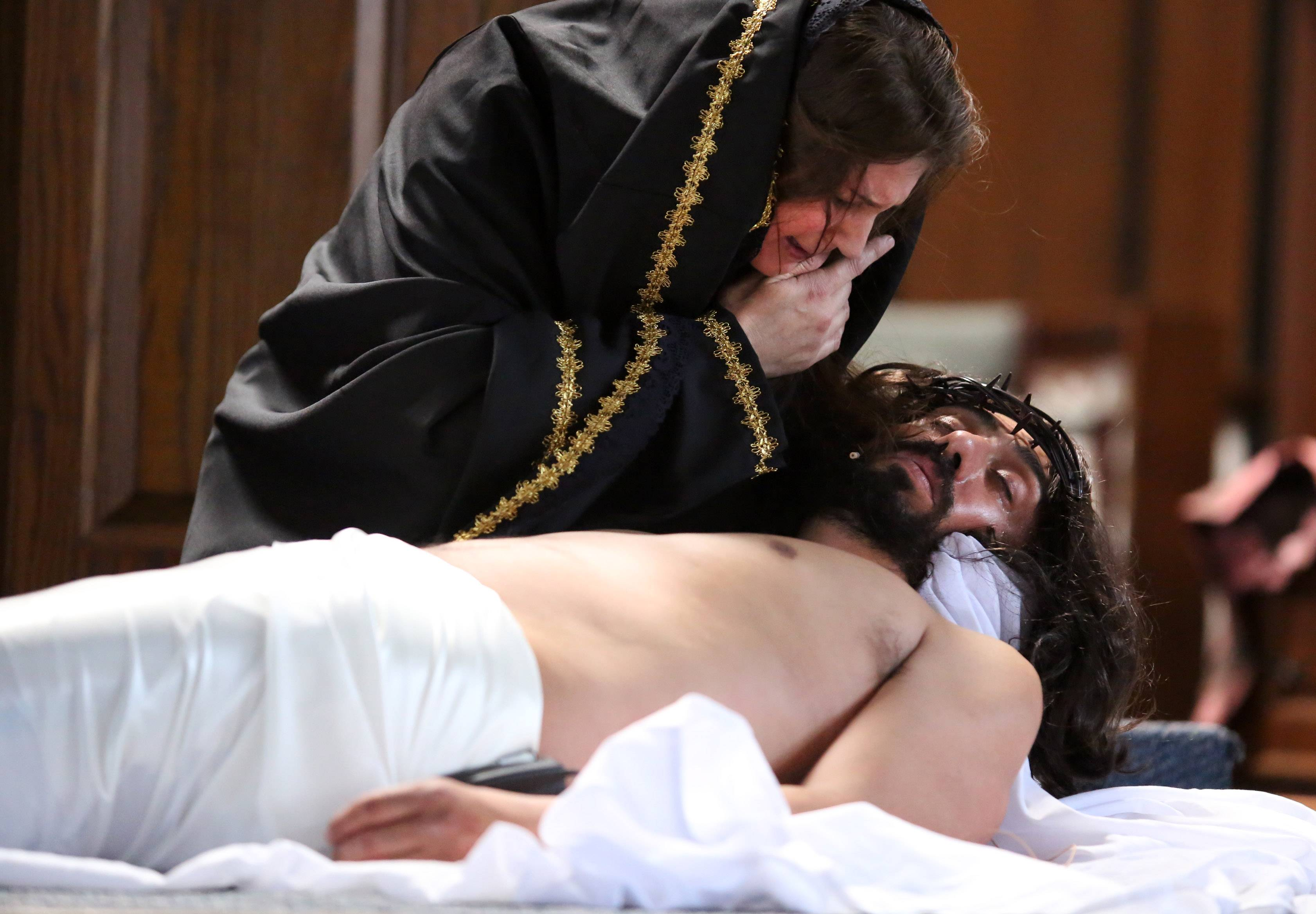 Mary, played by Mayela Correa, cries over her son, Jesus, portrayed by Miguel Angel Correa, after he is removed from the cross during a drama at Santa Maria del Popolo Catholic Church in Mundelein on Good Friday. It was the second consecutive year the husband and wife from Mundelein were in Via Crucis.