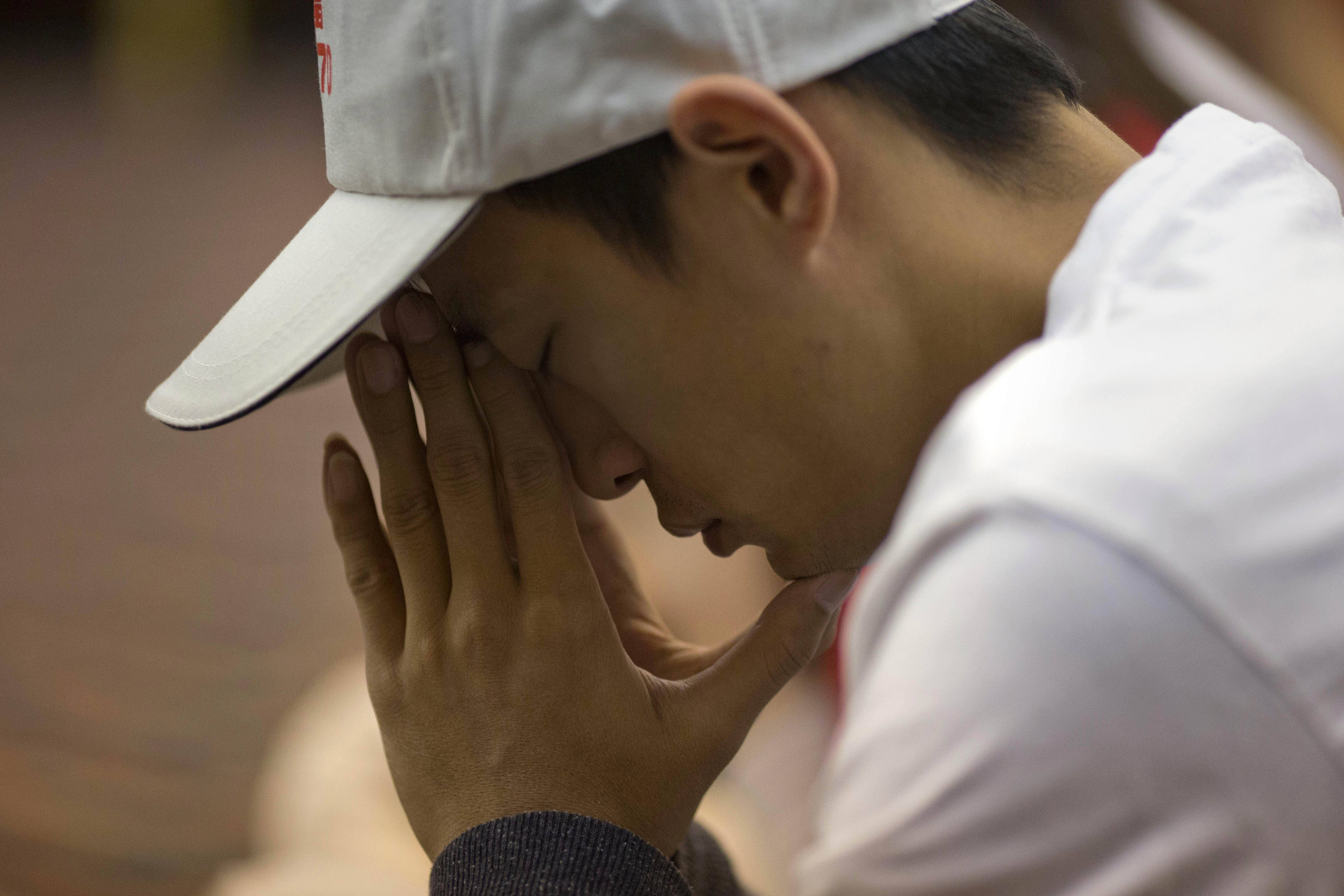 One of relatives of Chinese passengers on board the Malaysia Airlines Flight 370 prays Friday at a hotel conference room in Beijing, China. A robotic submarine headed back down into the depths of the Indian Ocean on Friday to scour the seafloor for any trace of the missing Malaysian jet one month after the search began off Australia's west coast, as data from the sub's previous missions turned up no evidence of the plane.