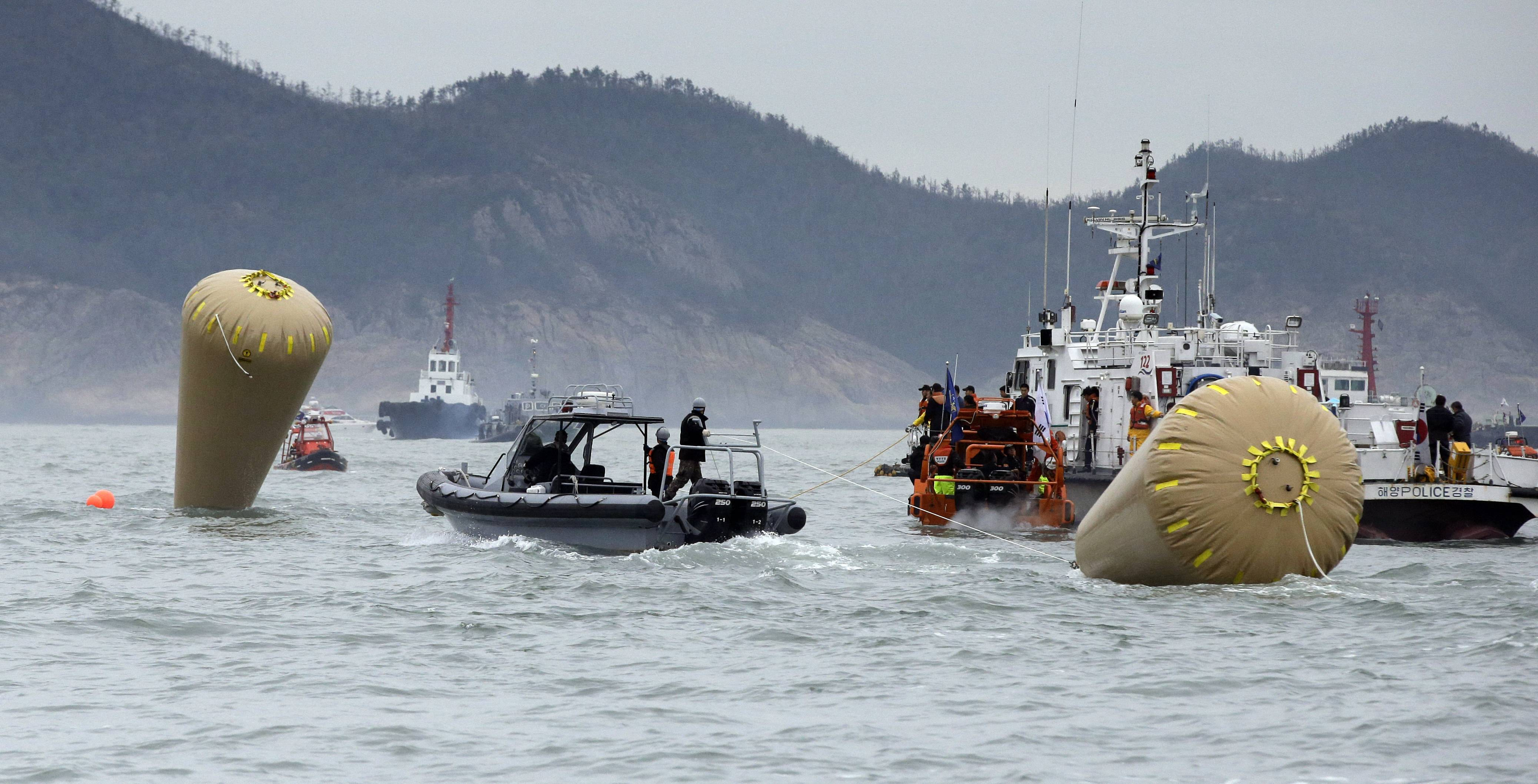 A buoy, right, is towed Friday by a South Korean Navy boat to be installed in addition to the other one, left, to mark the sunken 6,852-ton ferry Sewol in the water off the southern coast near Jindo, south of Seoul, South Korea. Rescuers scrambled to find hundreds of ferry passengers still missing Friday and feared dead, as fresh questions emerged about whether quicker action by the captain of the doomed ship could have saved lives.