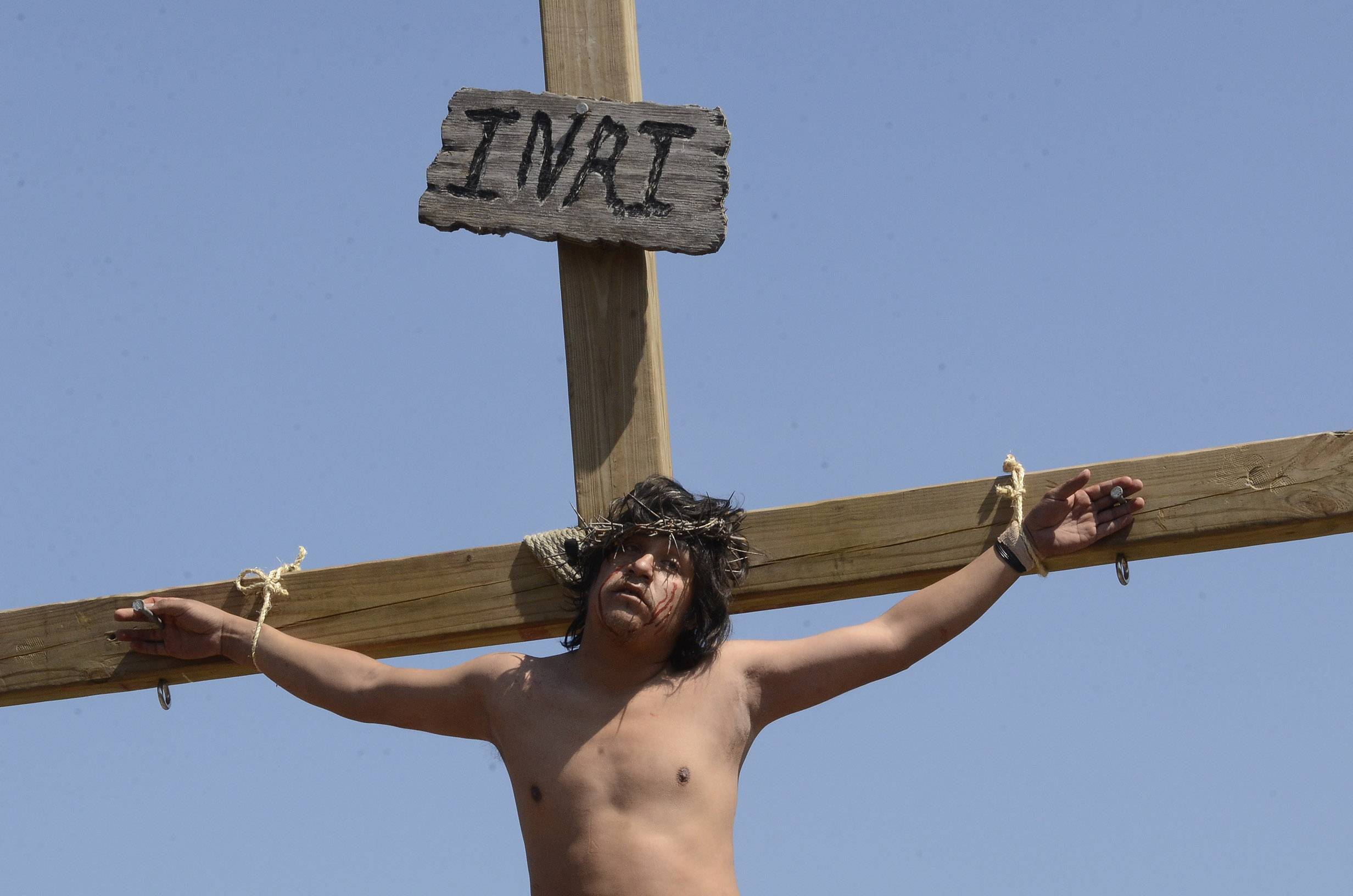 Rubin Callajo, an actor playing Jesus, performs the 12th Station of the Cross to signify Jesus dying on the cross during a re-enactment on Good Friday at Mision San Juan Diego in Arlington Heights.