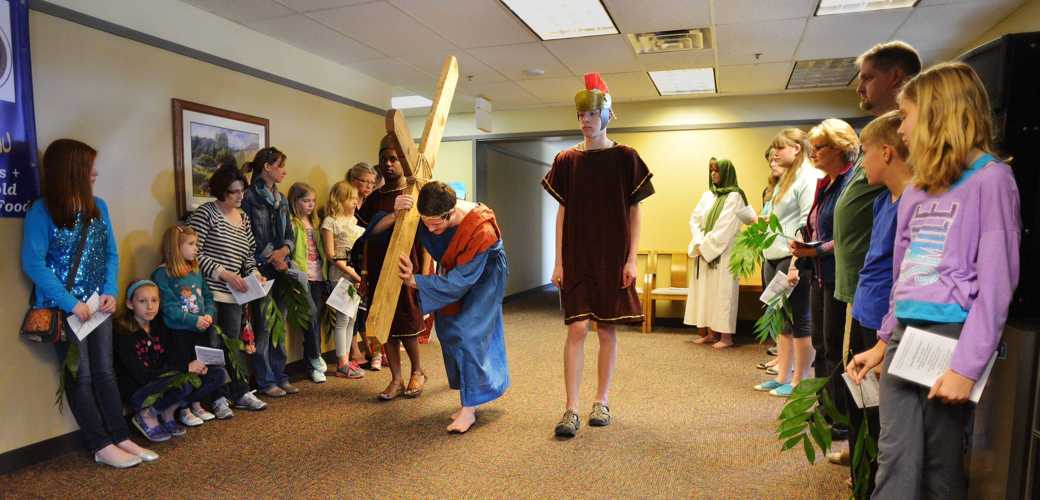 Members of Alleluia! Lutheran Church in Naperville observe Good Friday with actors and members of the congregation going to different parts of the building to act out Jesus' journey to the cross. In this scene, Jesus, as portrayed by Conor Hughes, carries his cross accompanied by Roman guards.