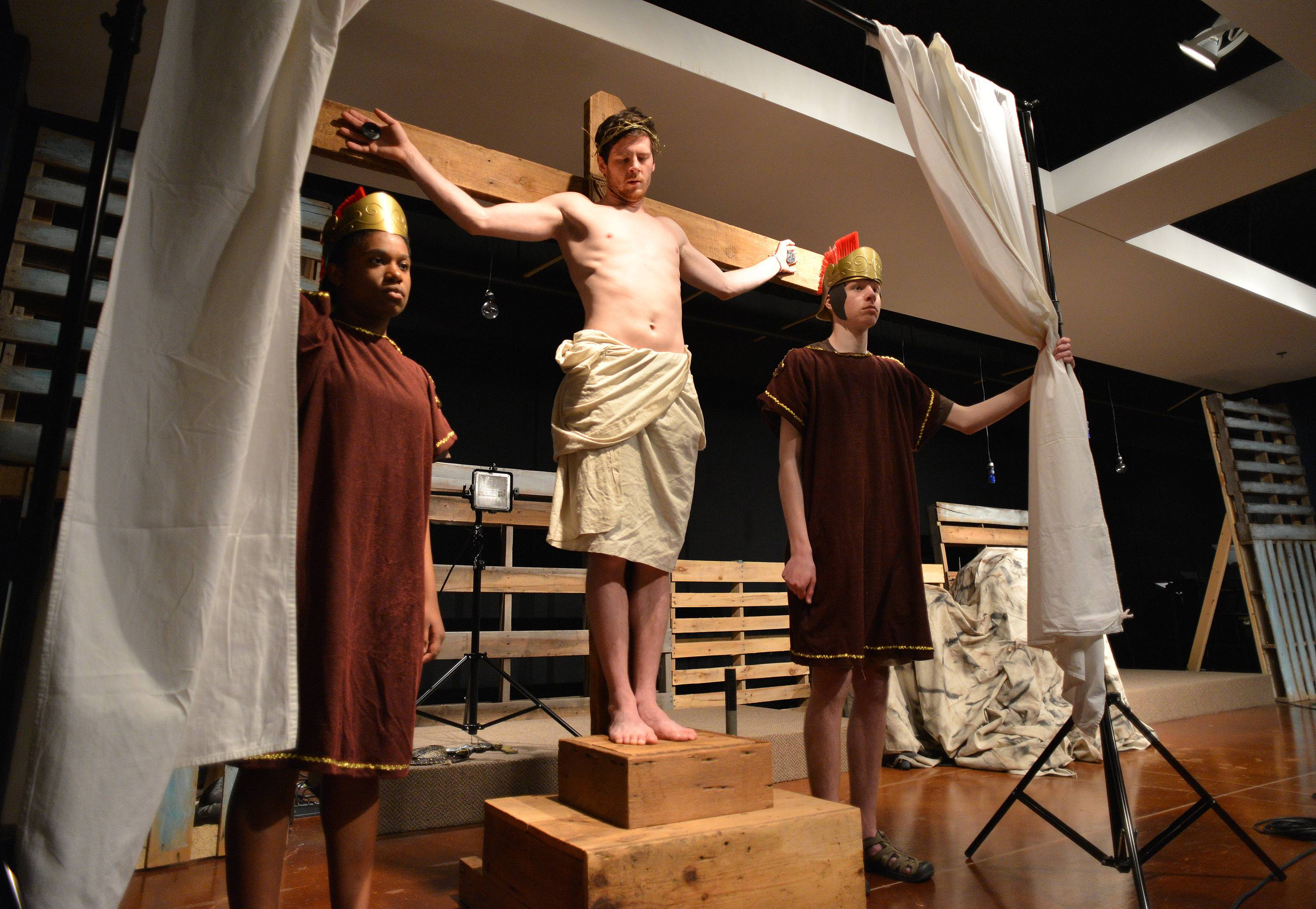 The last scene in Alleluia Lutheran Church's Passion Week Experience is Jesus on the cross, guarded by Roman soldiers portrayed by Taya Finch, left, and Nick Duesing. Jesus is portrayed by Conor Hughes.