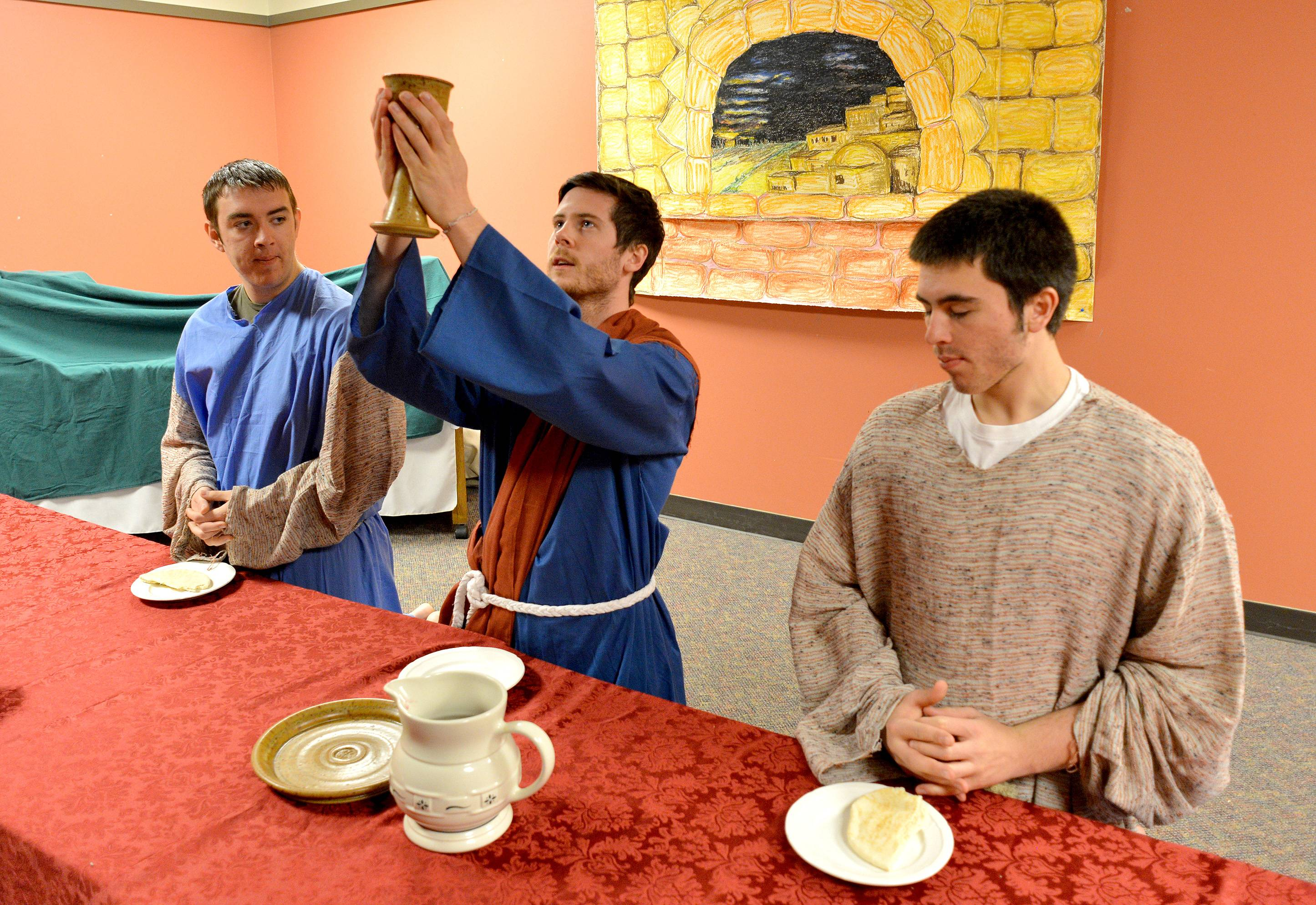 Jesus, portrayed by Conor Hughes, center, participates in the Last Supper with two of his disciples, Peter portrayed by Nathanael Juliot, left, and Judas, portrayed by Sean Bary during Good Friday observations at Naperville's Alleluia! Lutheran Church.