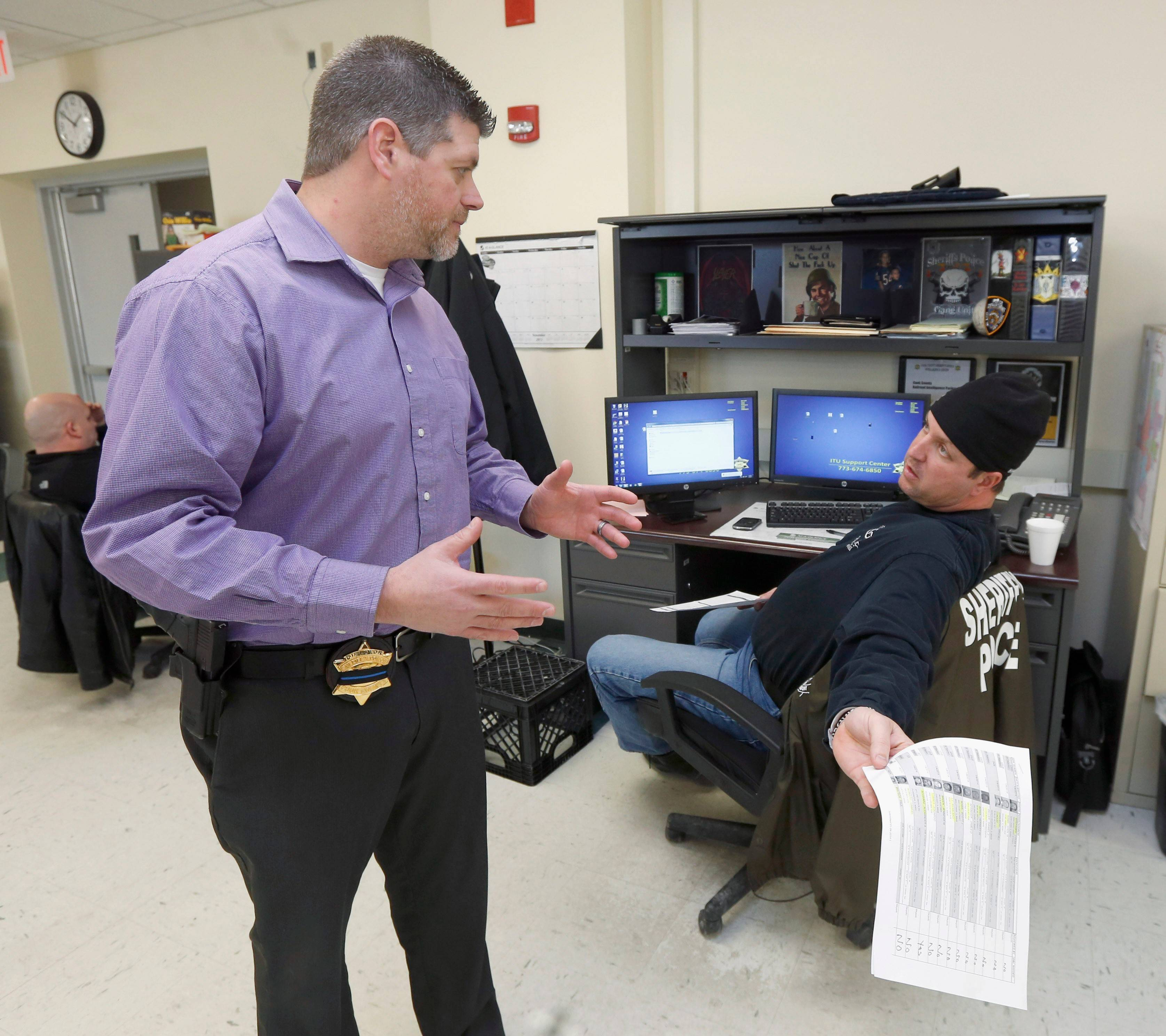 John Blair, left, executive director of the Cook County Sheriff's Office Intelligence Center, consults with Officer John Slepski about a firearms background check Slepski is performing at the center in Chicago.