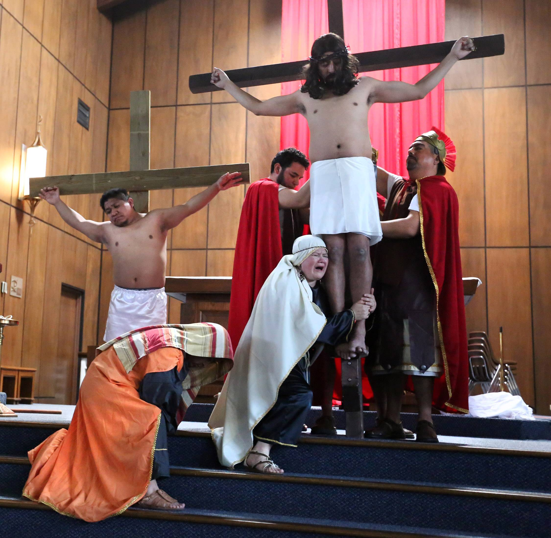 Mary Magdalene, portrayed by Emilia Urbe, clings to the legs of Jesus, who was played by Miguel Angel Correa. The Mundelein residents appeared in Via Crucis at Santa Maria del Popolo Catholic Church in Mundelein on Good Friday. The annual drama illustrates the passion and death of Jesus Christ.