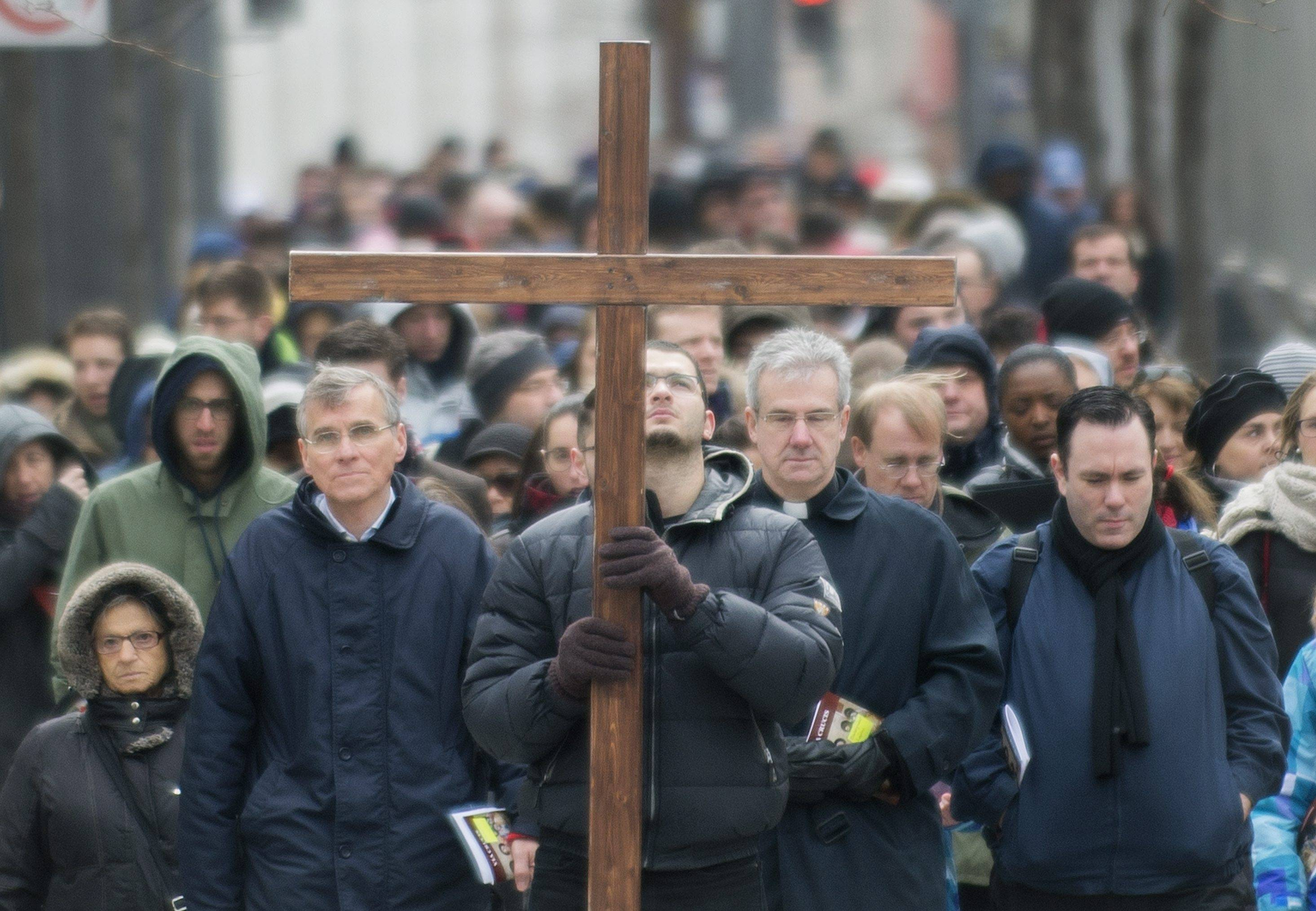 A man walks with a crucifix along with the faithful as they participate in the Way of the Cross on Good Friday in Montreal.