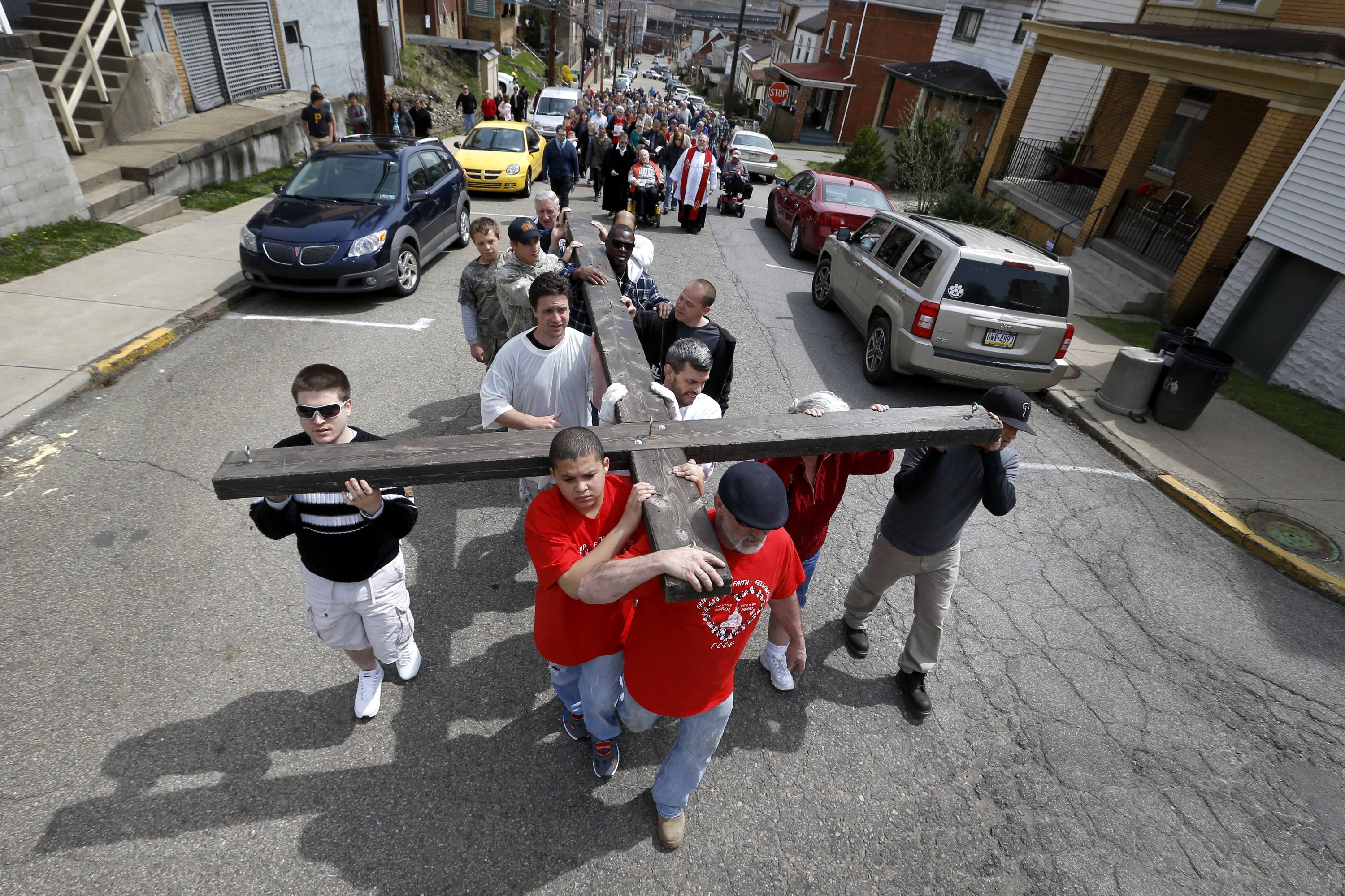 "Volunteers carrying a wooden cross walk in a procession through the streets of Etna, Pa., a Pittsburgh suburb, on Good Friday, as part of their annual ""Drama of The Cross"". Clergymen from Christian churches in the borough organize a trek with volunteers carrying the wooden cross through borough streets to the cemetery as part of their services."
