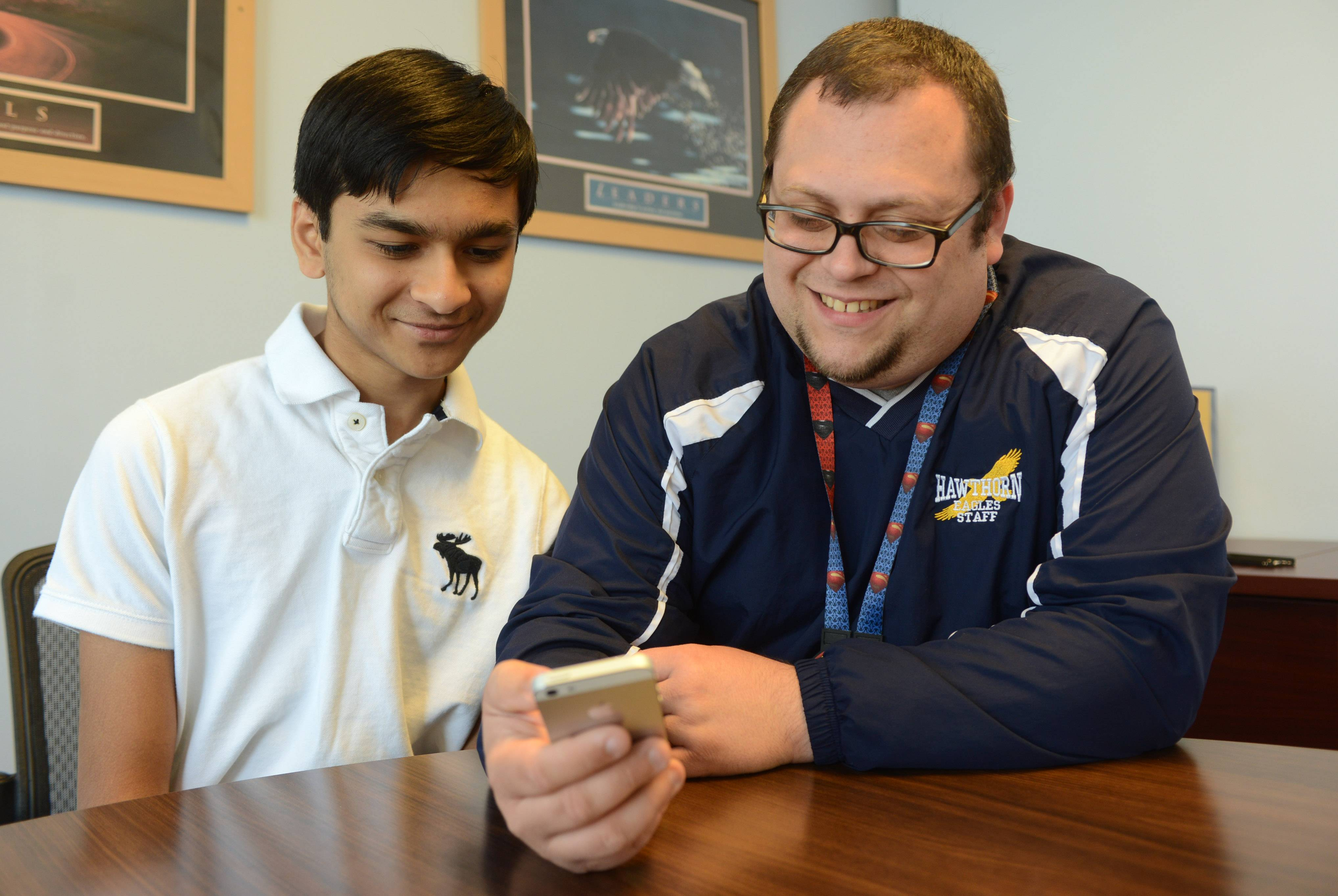 Hawthorn Middle School North language arts teacher John Reid, right, checks out Anmol Parande's InstaQuiz trivia app at the Vernon Hills school.