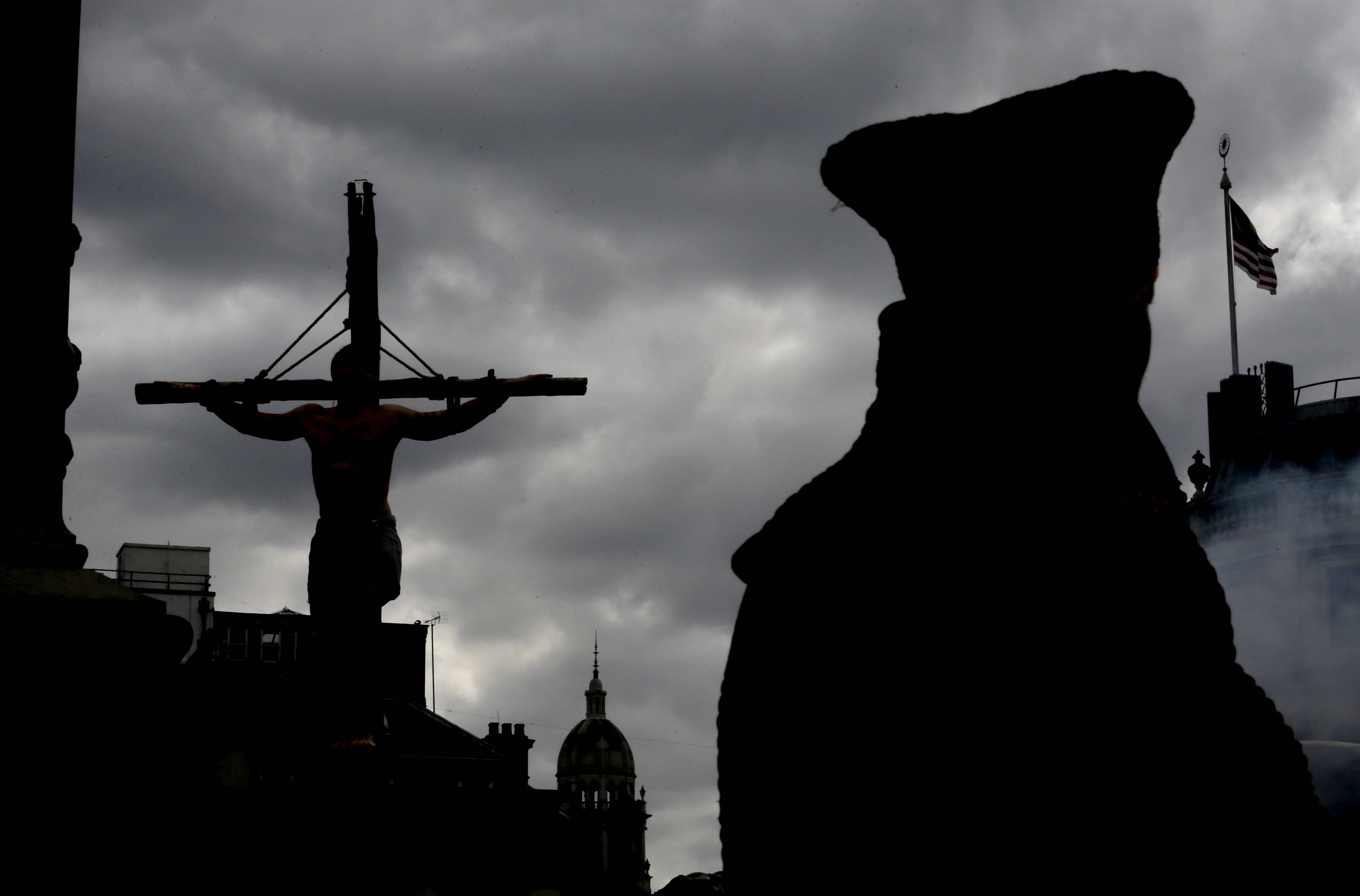 An actor is silhouetted hanging on a cross during a performance Friday in Trafalgar Square in London. The play called 'The Passion of Jesus' was a free performance depicting the betrayal, capture, trial, crucifixion and resurrection of Jesus, performed by the Wintershall players.