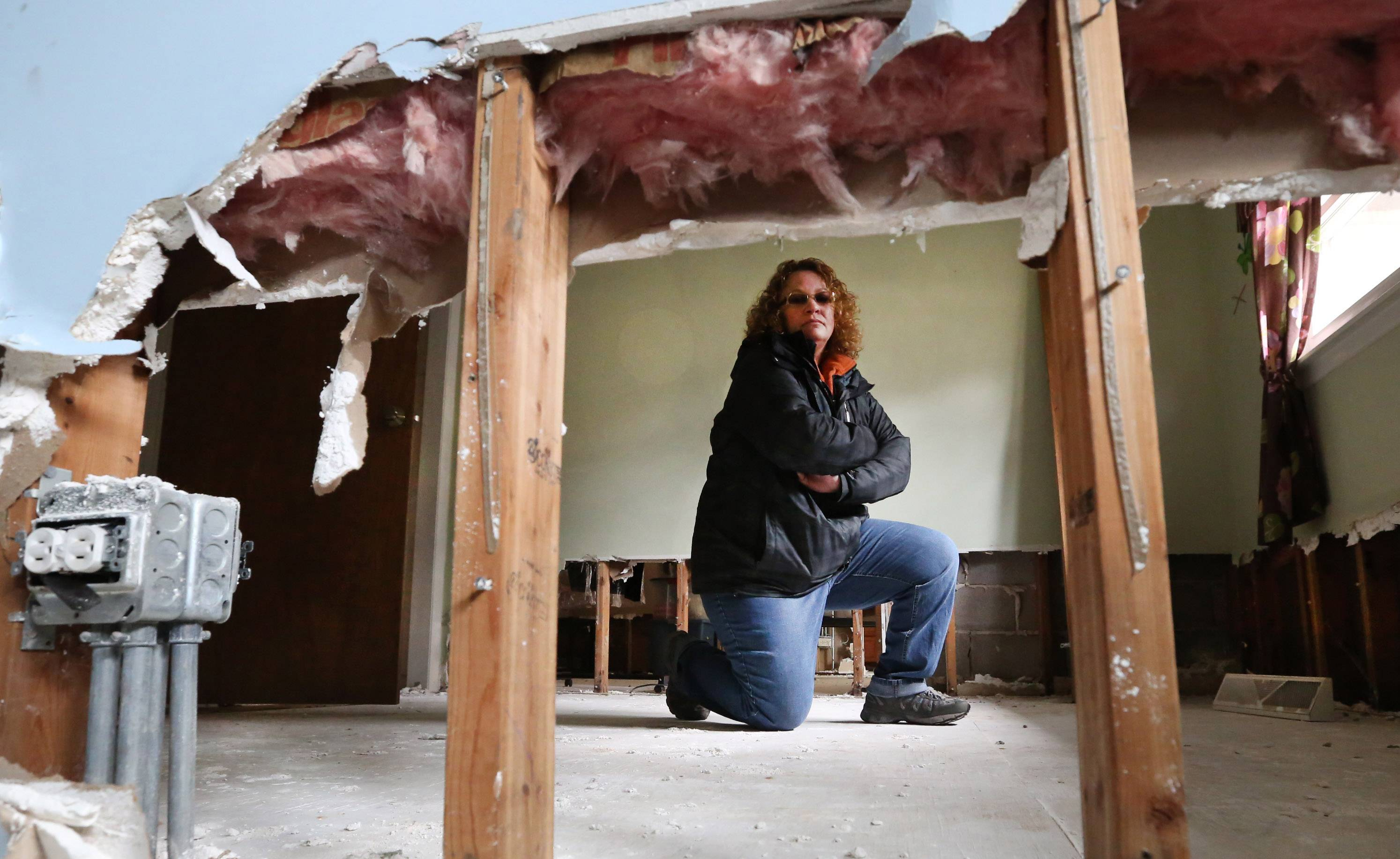 Heather Roppel looks through the wall between two bedrooms in her flood-damaged Des Plaines home this week, a year after floods struck her neighborhood. Roppel's home is one of 21 in Des Plaines eligible for a federal buyout.