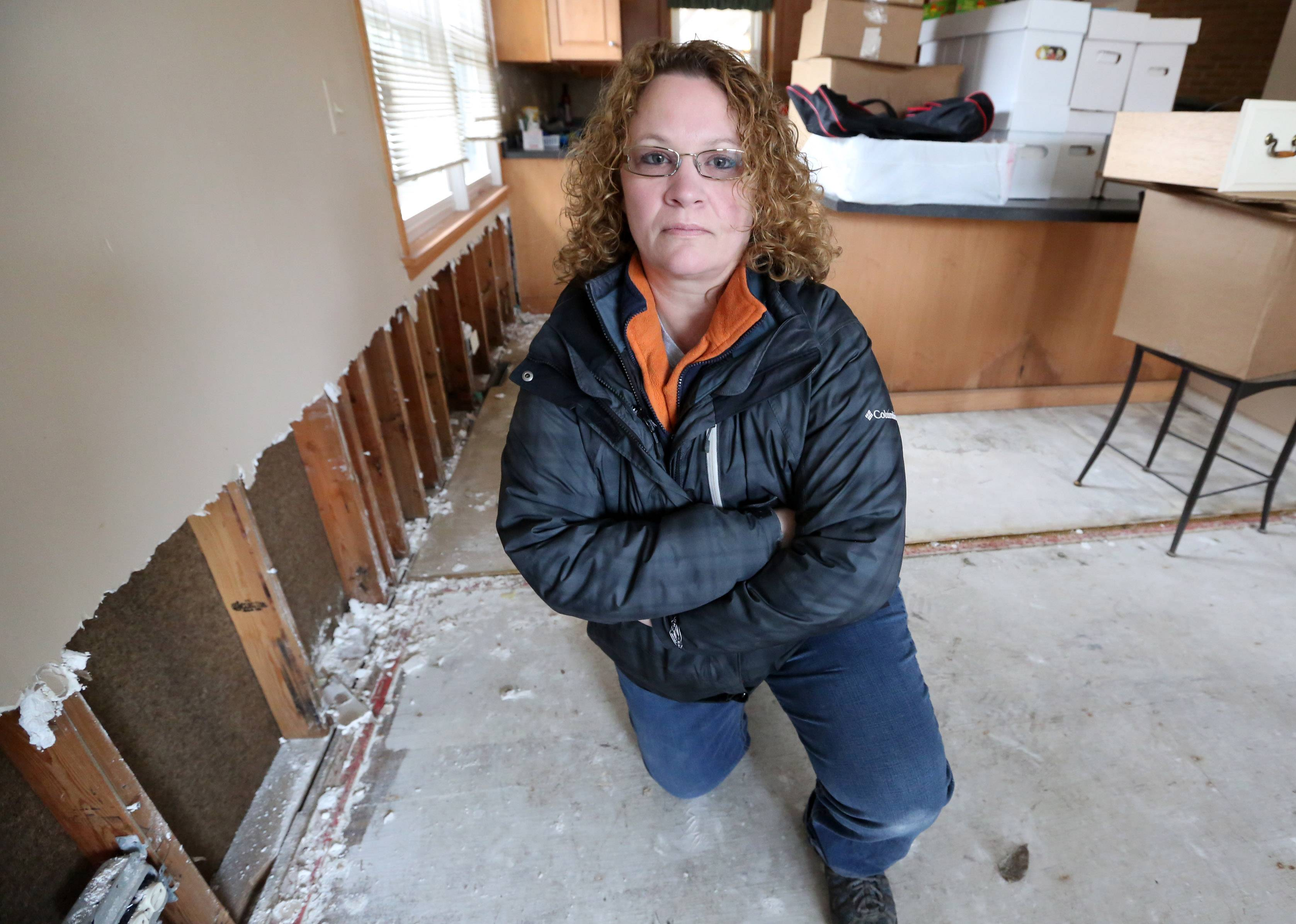 Heather Roppel stands in her flood-damaged Des Plaines home this week, a year after floods left the house under water and causing thousands of dollars worth of damage. Roppel's home is one of 21 in Des Plaines eligible for a federal buyout.