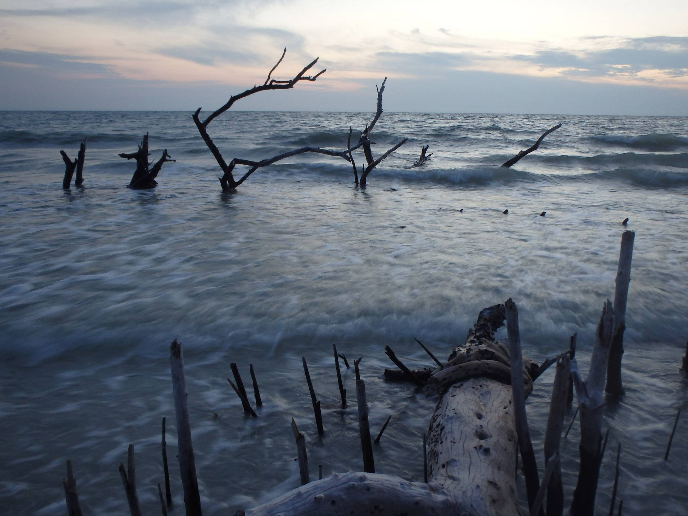 Waves create a ghostly atmosphere just before night sets in along Fort Meyers Beach during high tide at sunset.