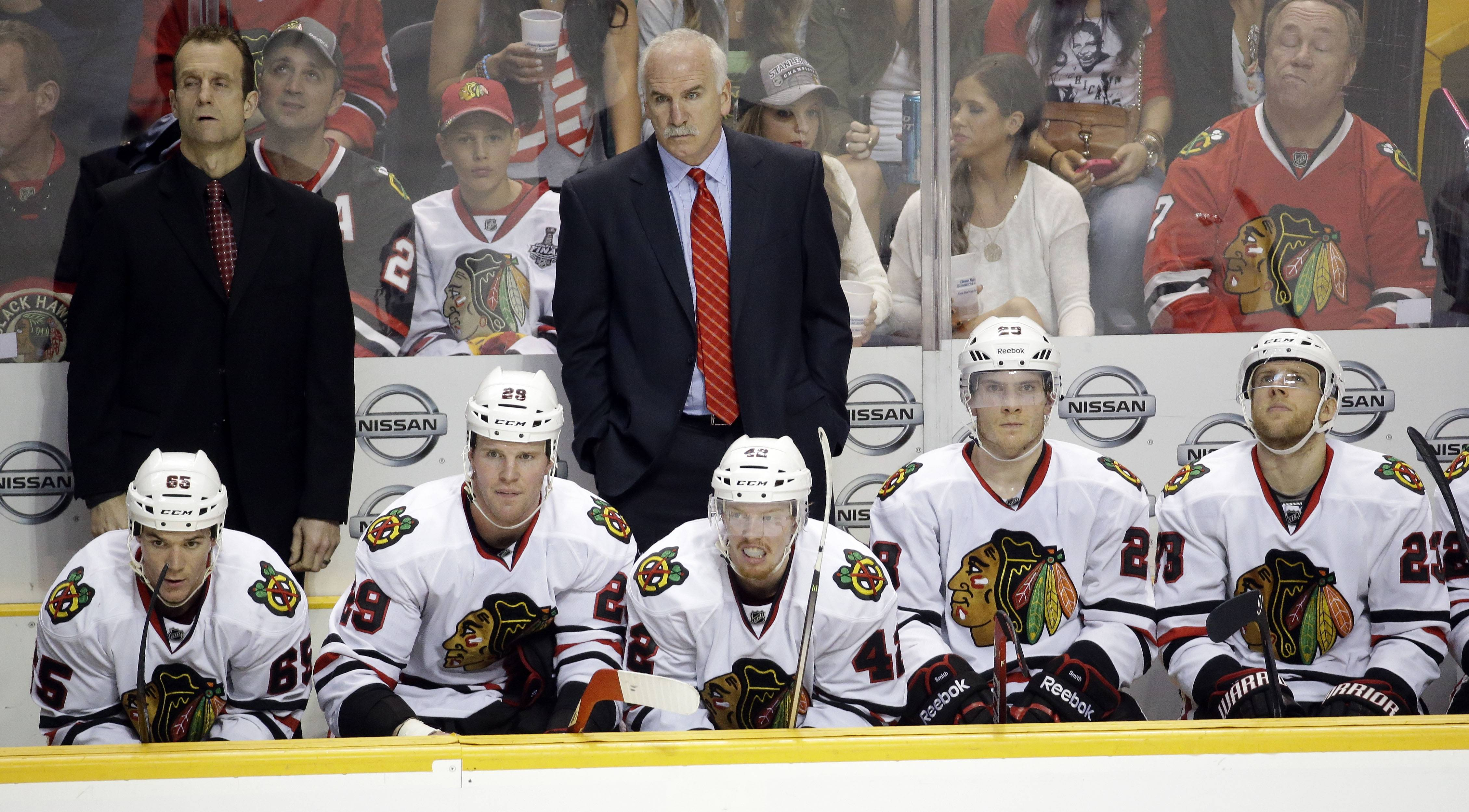 Chicago Blackhawks coach Joel Quenneville, center, and assistant coach Jamie Kompon, left, watch the action in the final seconds of an NHL hockey game against the Nashville Predators Saturday, April 12, 2014, in Nashville, Tenn. The Predators won 7-5.