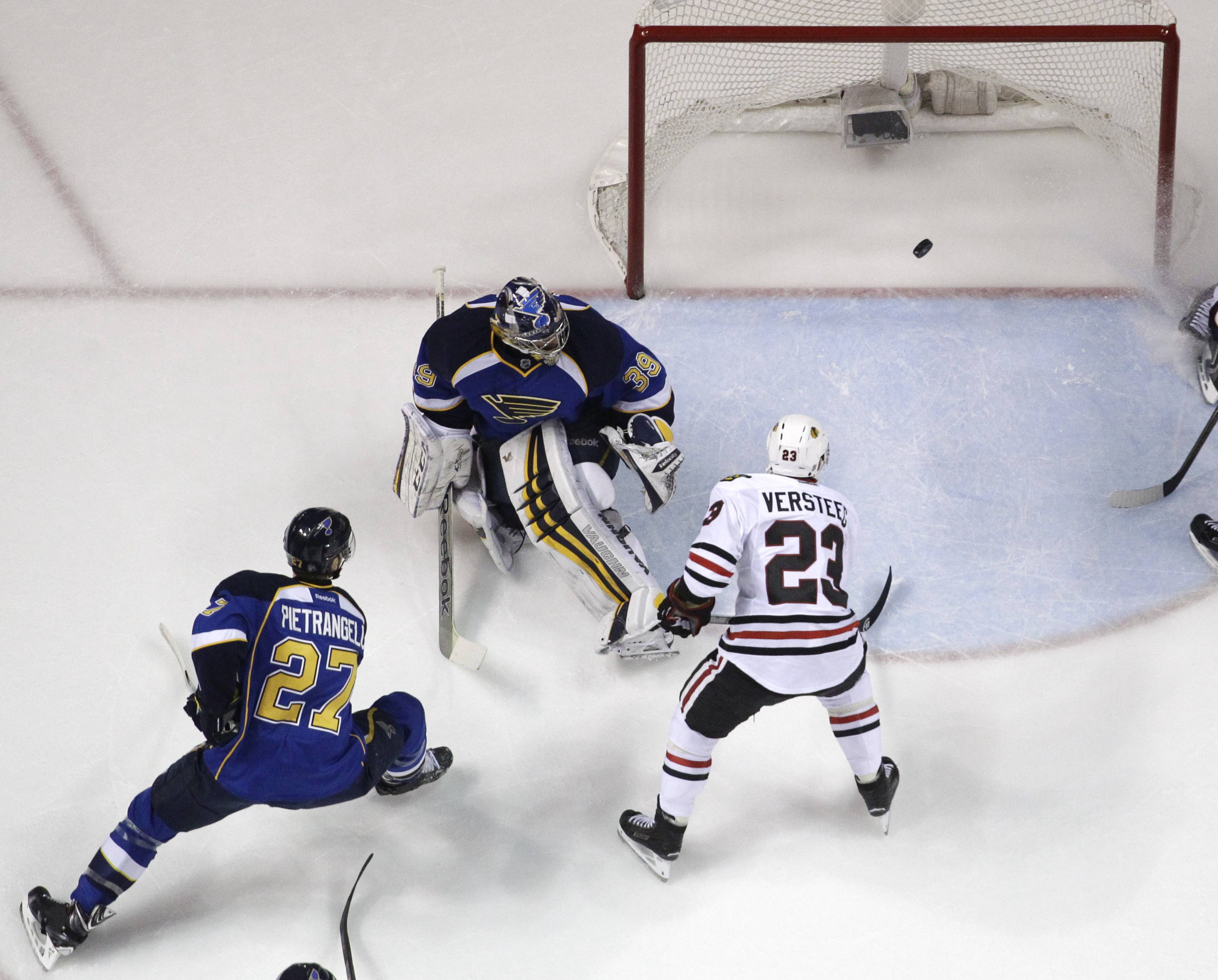 Chicago Blackhawks' Kris Versteeg (23) scores past St. Louis Blues goalie Ryan Miller and Blues' Alex Pietrangelo (27) during the first period in Game 1 of a first-round NHL hockey Stanley Cup playoff series Thursday, April 17, 2014, in St. Louis.
