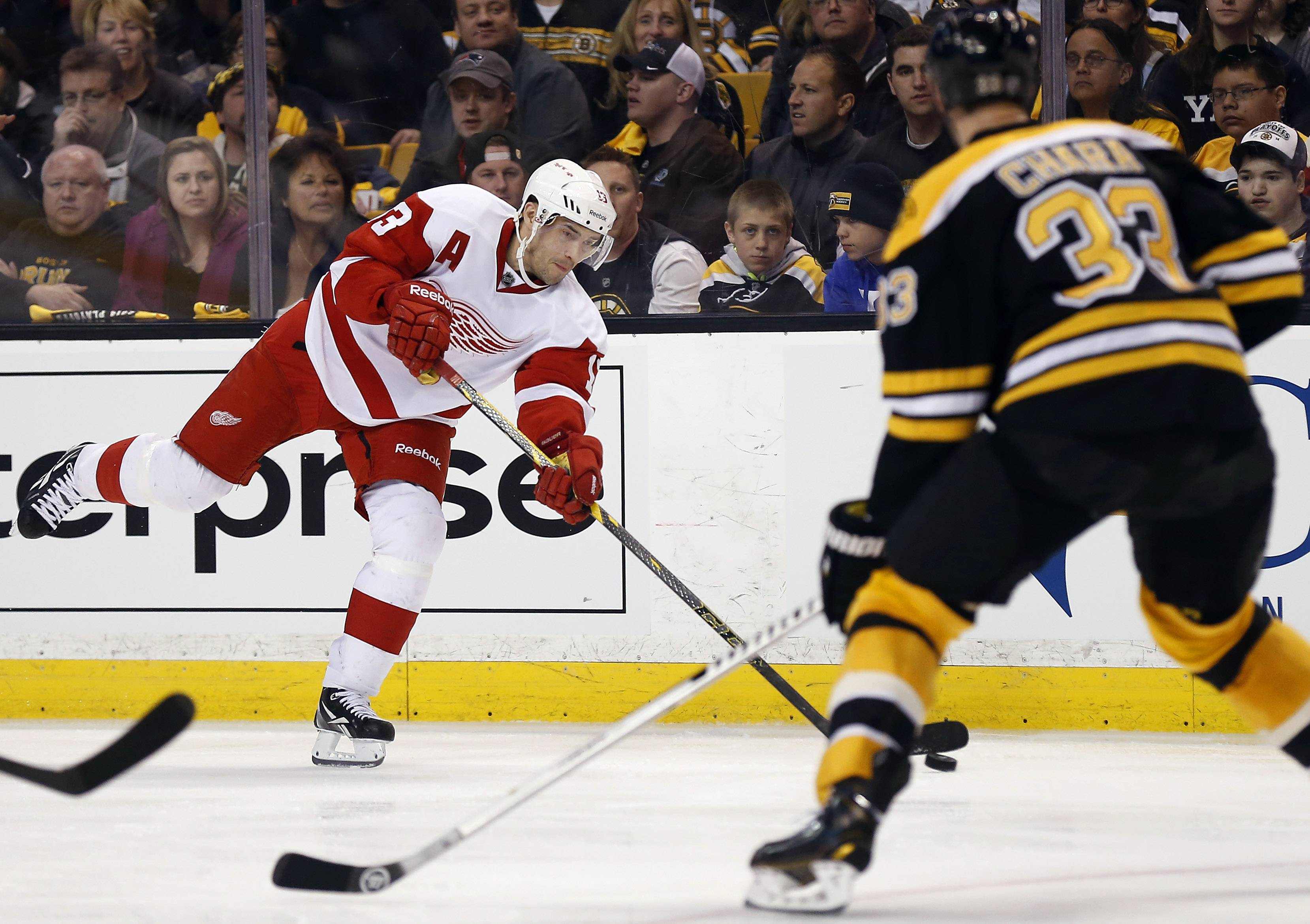 Detroit Red Wings' Pavel Datsyuk lets go a shot as Boston Bruins defenseman Zdeno Chara (33) defends during the third period of Detroit's 1-0 win in Game 1 of a first-round NHL playoff hockey series, in Boston on Friday, April 18, 2014.