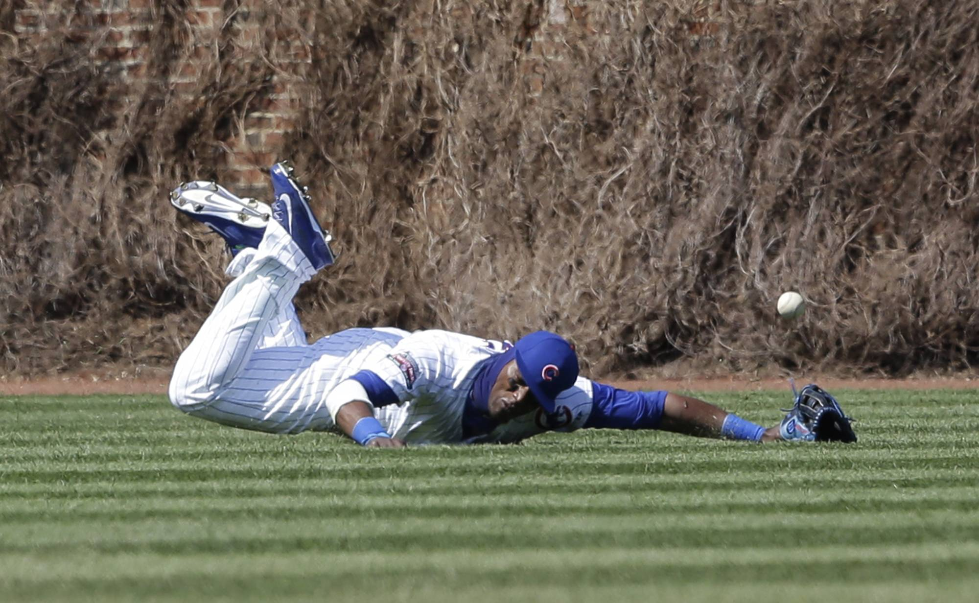 Cubs left fielder Junior Lake can' t make the catch on a double hit by Cincinnati Reds' Billy Hamilton during the fifth inning of a baseball game in Chicago, Friday, April  18, 2014.